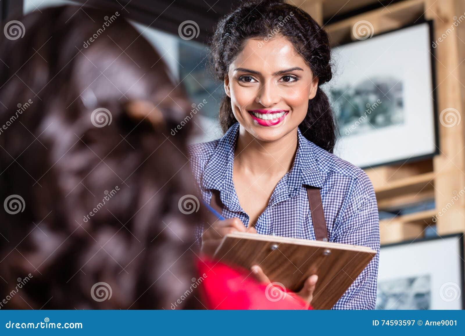 Servitris i den indiska restaurangen som tar beställningar