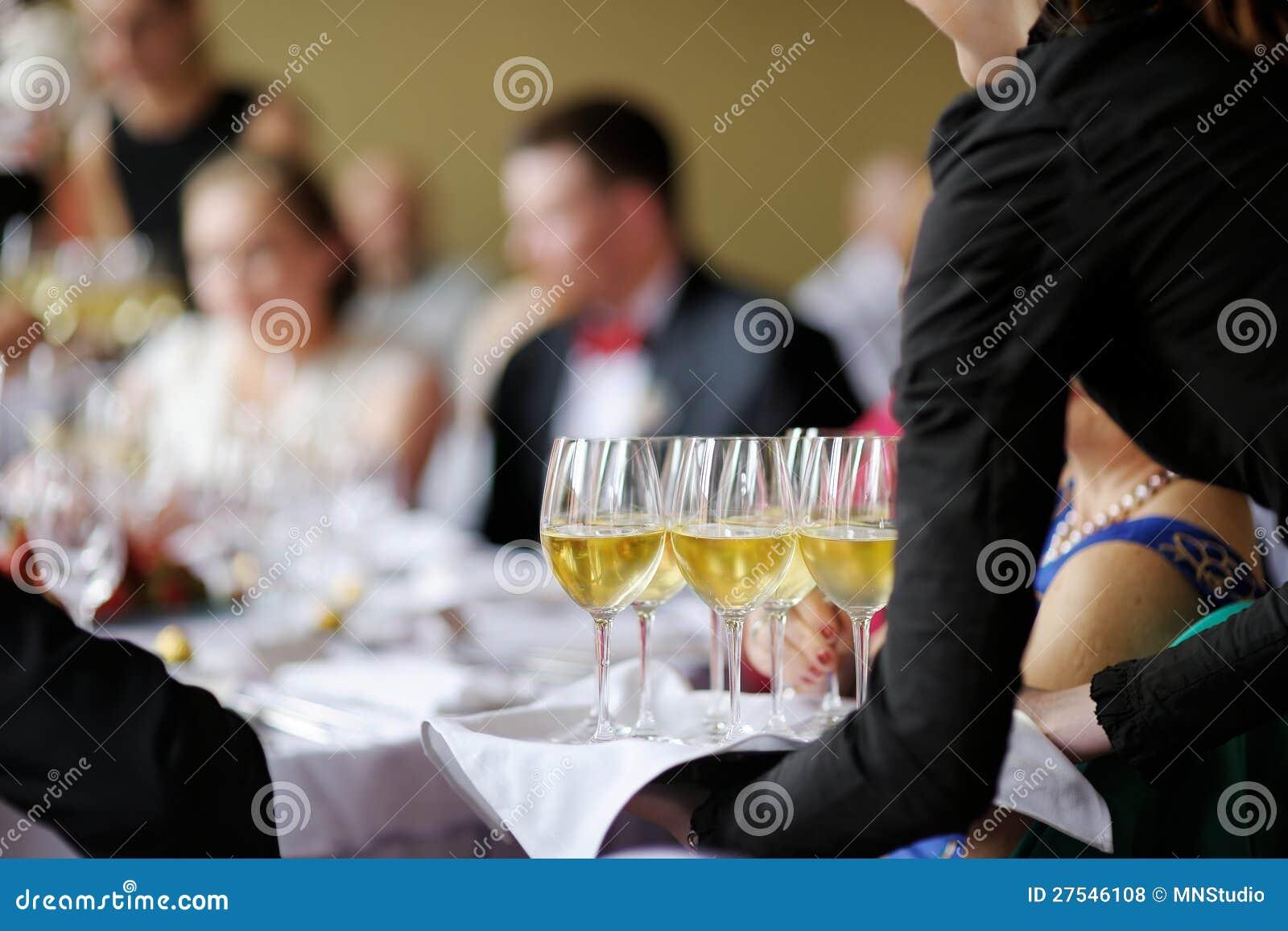 Servitris med maträtten av champagneexponeringsglas