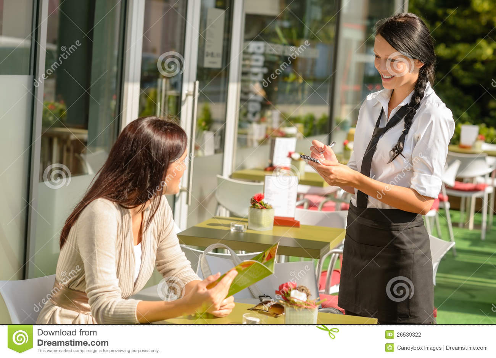Servitris som tar kvinna beställning på cafestången