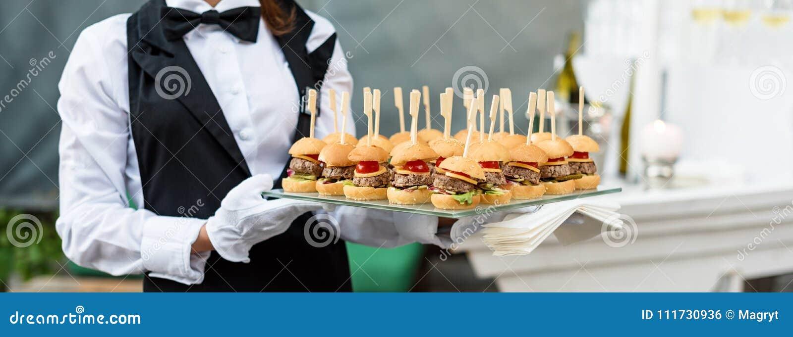 Servizio di approvvigionamento Cameriere che porta un vassoio di aperitivi Partito all aperto con cibo da mangiare con le mani, m