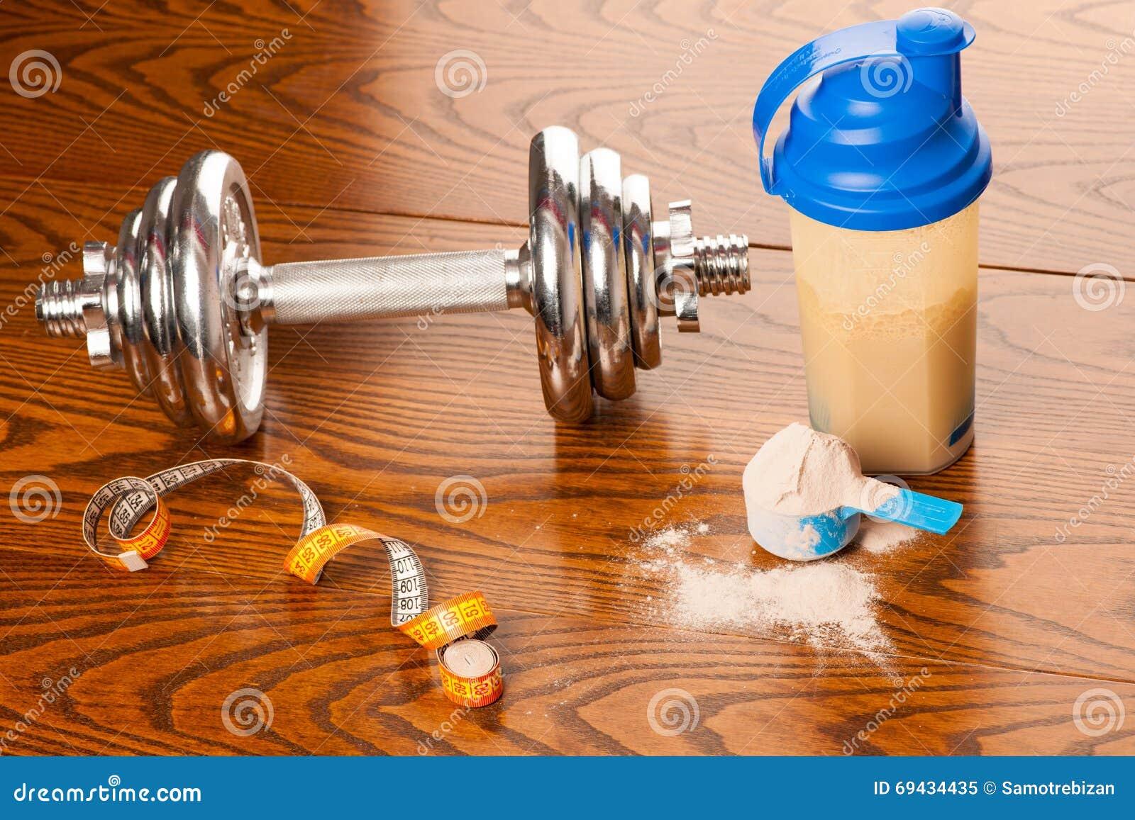 Serwatki proteiny proszek w miarce, dumbbell, metrowej taśmie s i klingerycie,