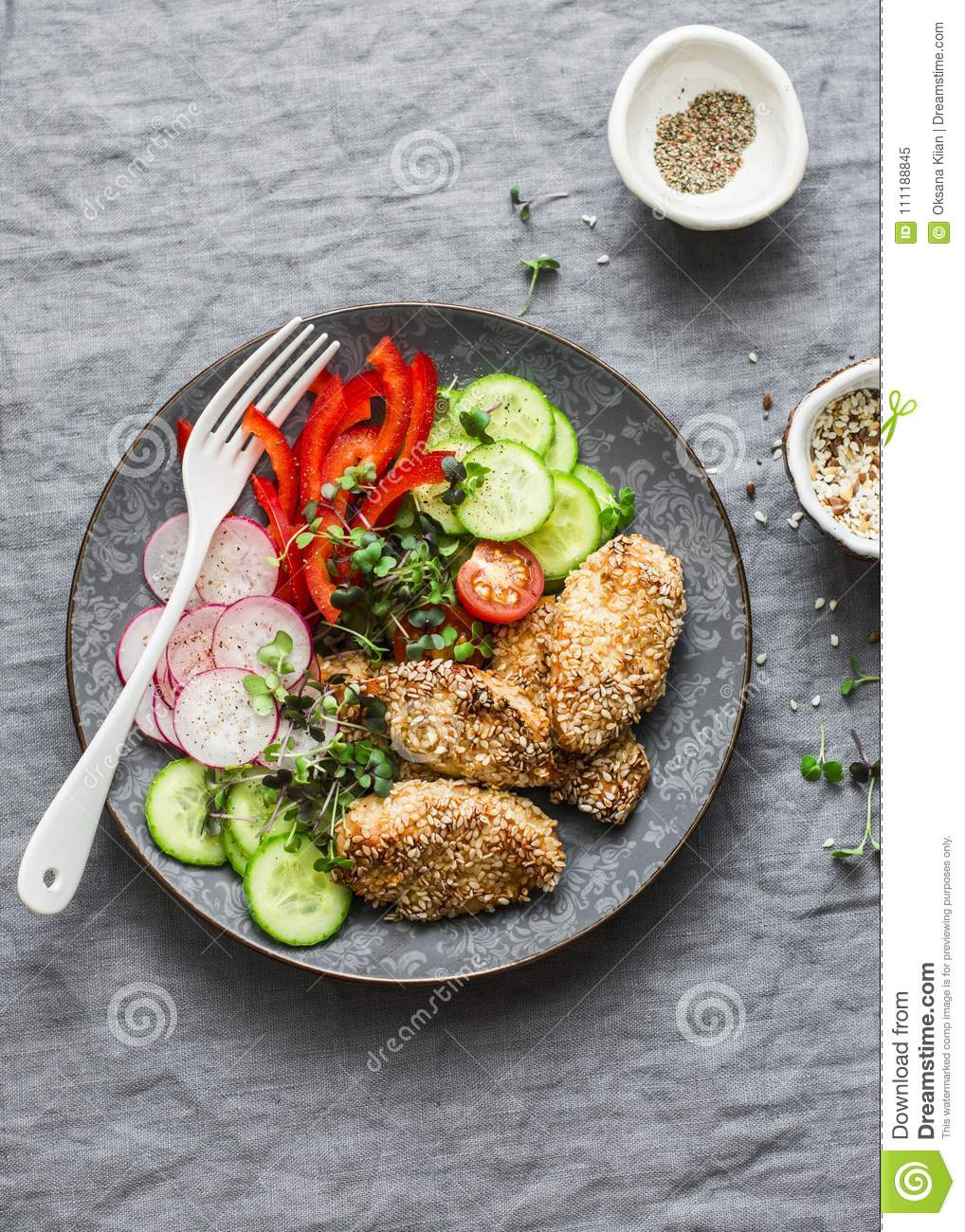 Sesame breading teriyaki baked chicken breast and fresh vegetables. Baked chicken and tomatoes, cucumbers, peppers, radishes, micr