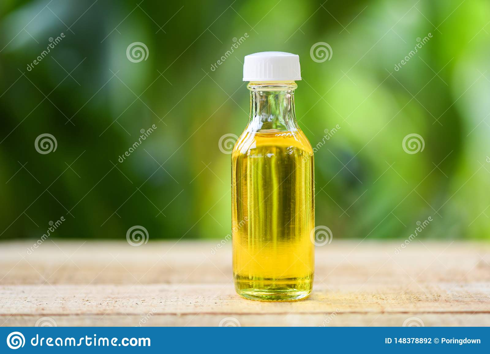Sesame oil in glass bottles on wooden and nature green