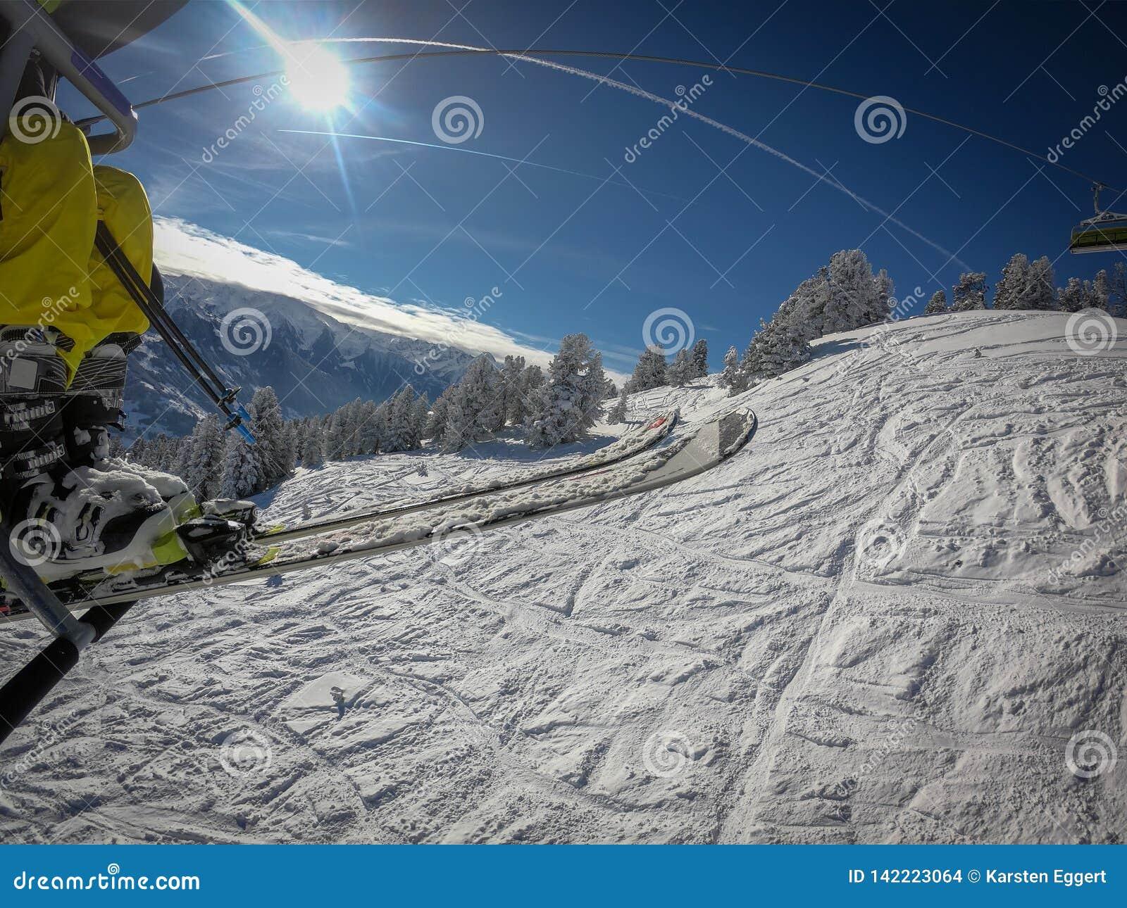 Sesselbahn nimmt Sie über dem Skigebiet mit blauen Himmeln und weißen Steigungen