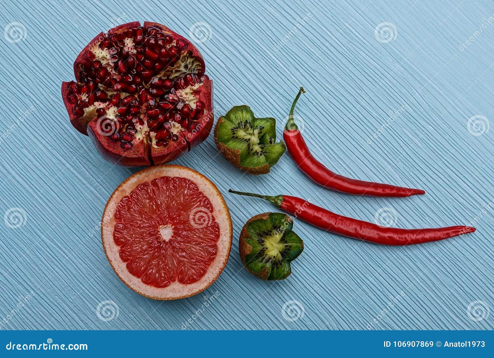 Set świeże dojrzałe owoc i czerwoni pieprze na błękitnym stole