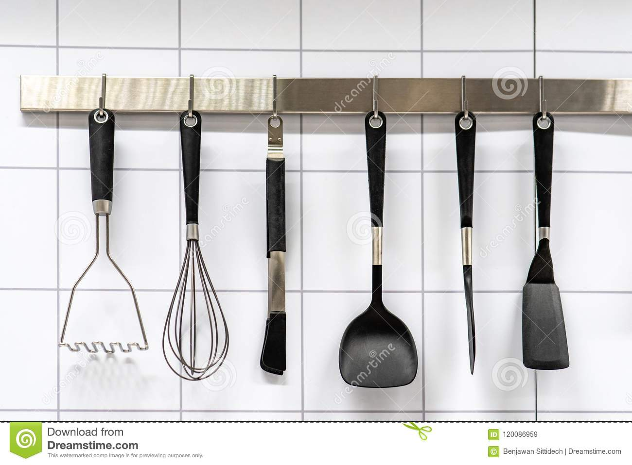 Set of black cooking utensils hanging on stainless bar on white modern ceramic wall tiles in the kitchen kitchenware or cookware concept