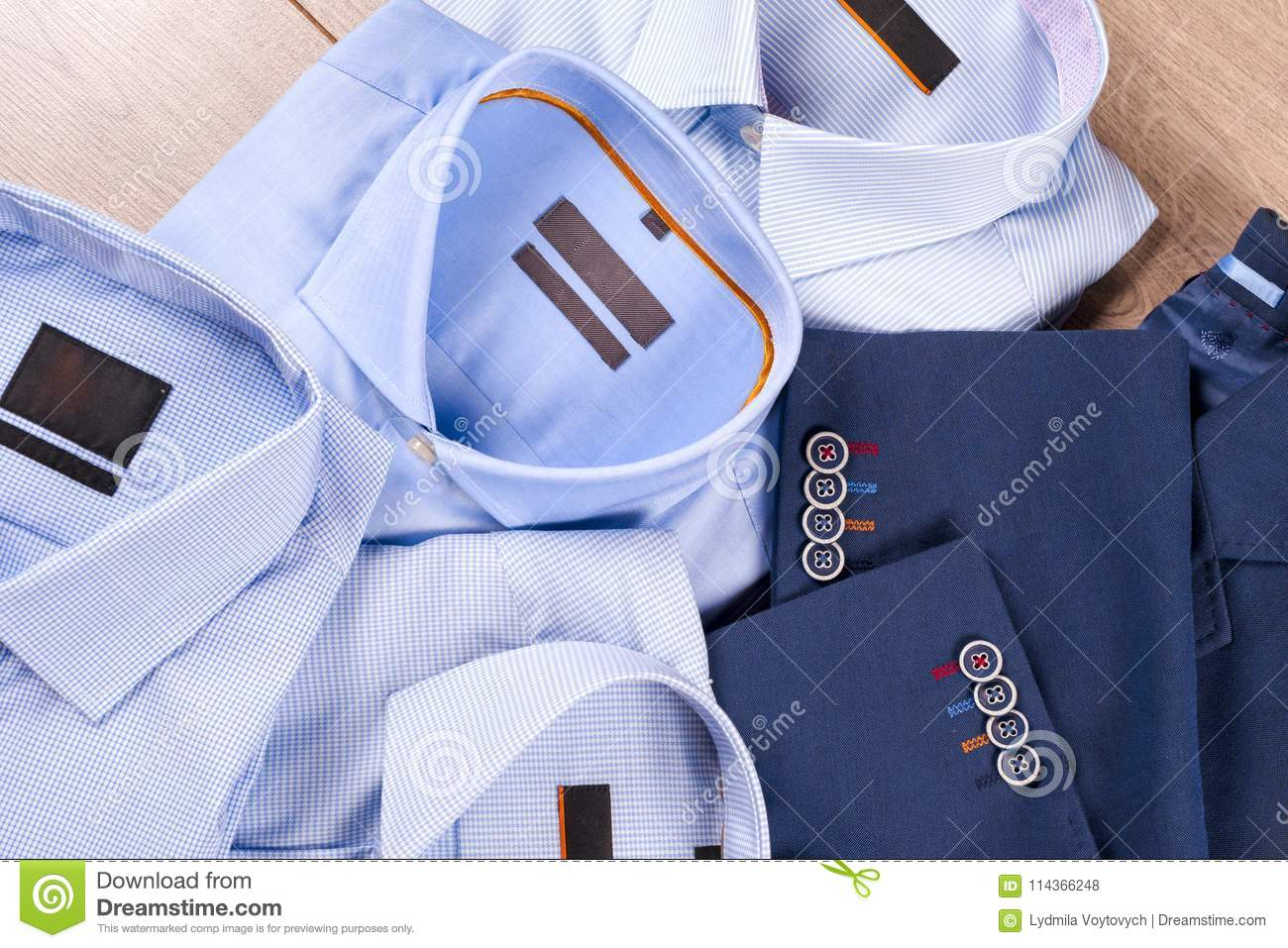 c0bc4646f1423 Set of classic mens clothes - blue suit, shirts, brown shoes, belt and tie  on wooden background. Fashion. Men`s accessories set. Top view.