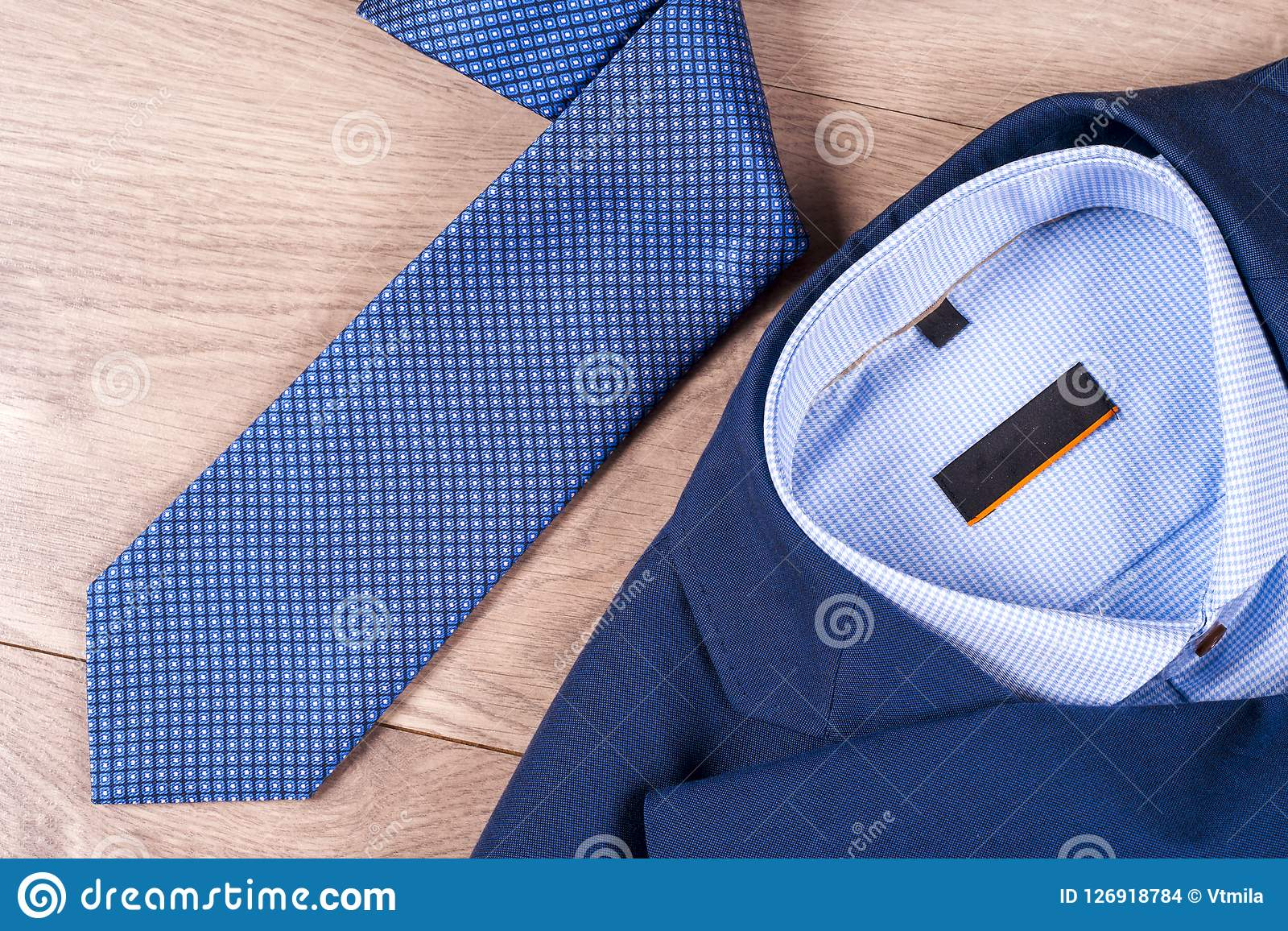 99819440 Set of classic mens clothes - blue suit, shirts, brown shoes, belt and tie  on wooden background. Fashion. Men`s accessories set. Top view.
