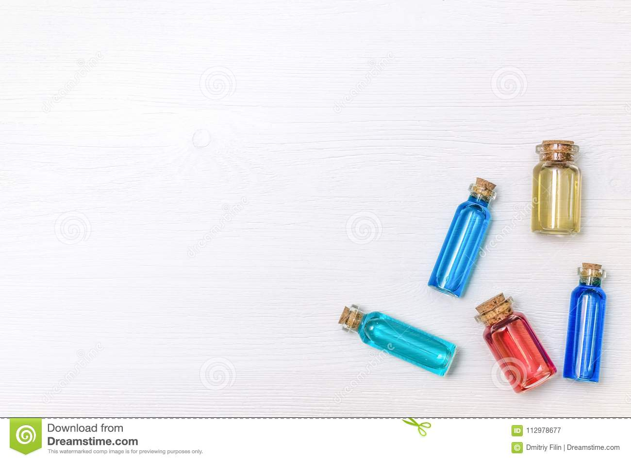Set of colorful essence oil tincture on white wooden background.