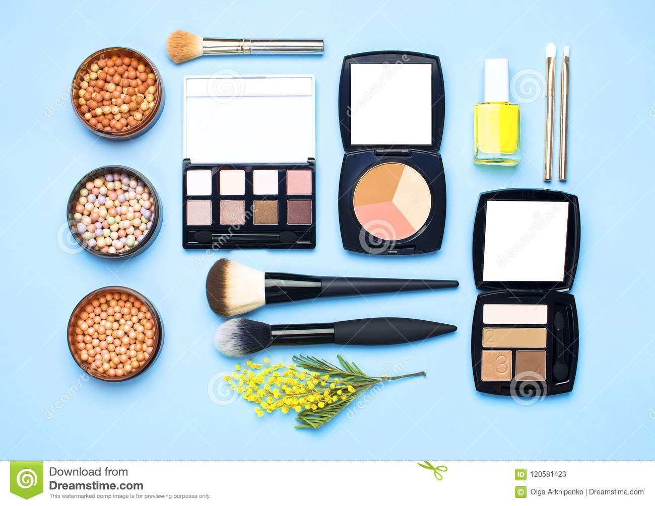 Set of decorative cosmetics for make-up Powder Rouge Eyeshadow Corrector Brushes and flowers of mimosa on blue background. Makeup
