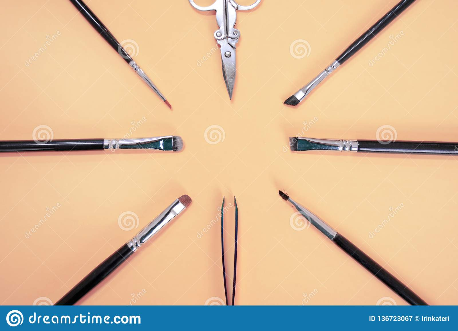 A set of different makeup artist brushes, tweezers and scissors lie in a circle with copyspace for text on pink color