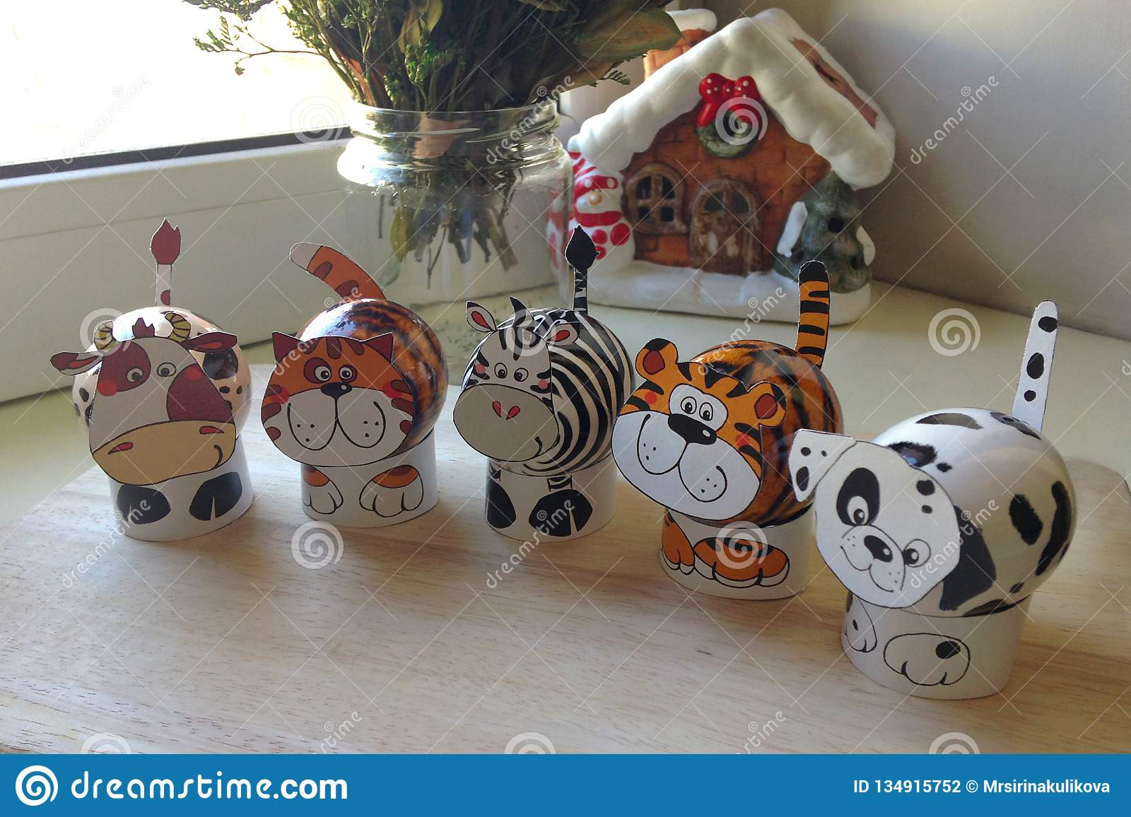 A set of Easter eggs in the form of animals on wooden board. In the background a bouquet of flowers in vase and a house figure