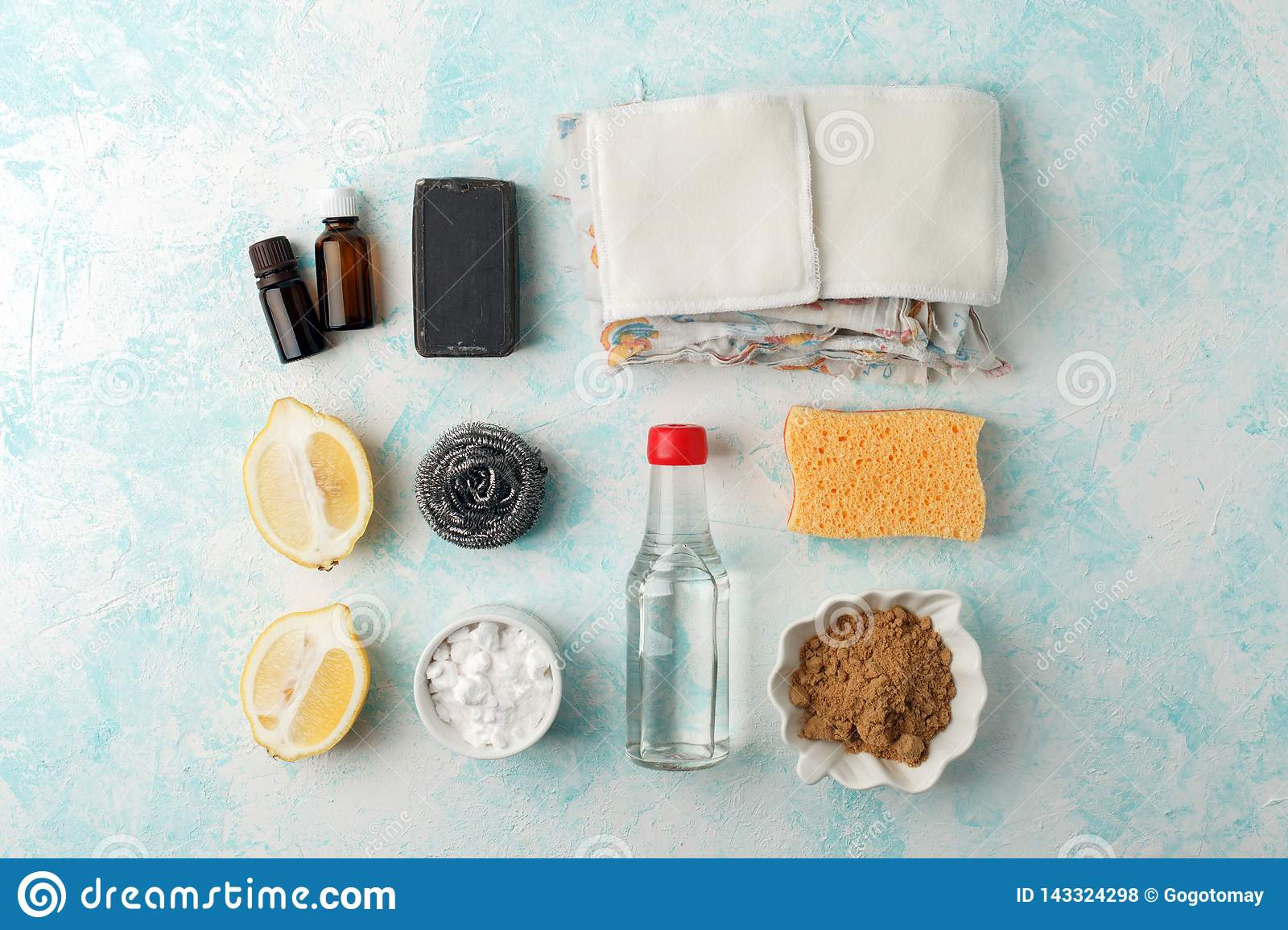 Set of eco-friendly natural cleaning products on wooden kitchen table: mustard, soda, essential oils, cellulose sponge, rags,
