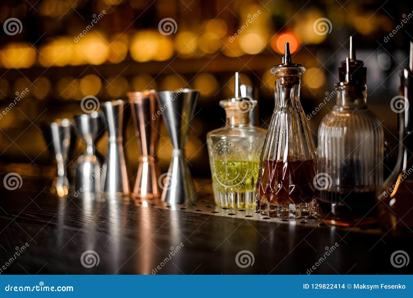 Set fachowi barmanów narzędzia wliczając osadzarek i małe butelki z trunkiem
