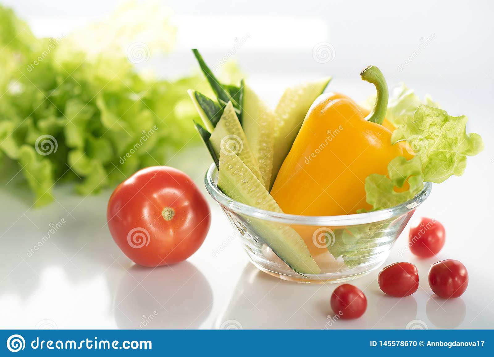 A set of fresh vegetables on a white plate, for the preparation of vegetable vegetarian salad. The background is white