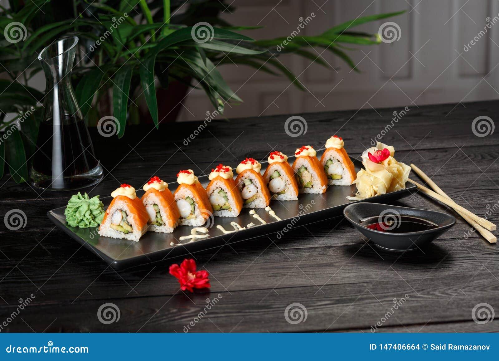 Set Fuji rolki na czarnym talerzu na czarnym drewnianym tle