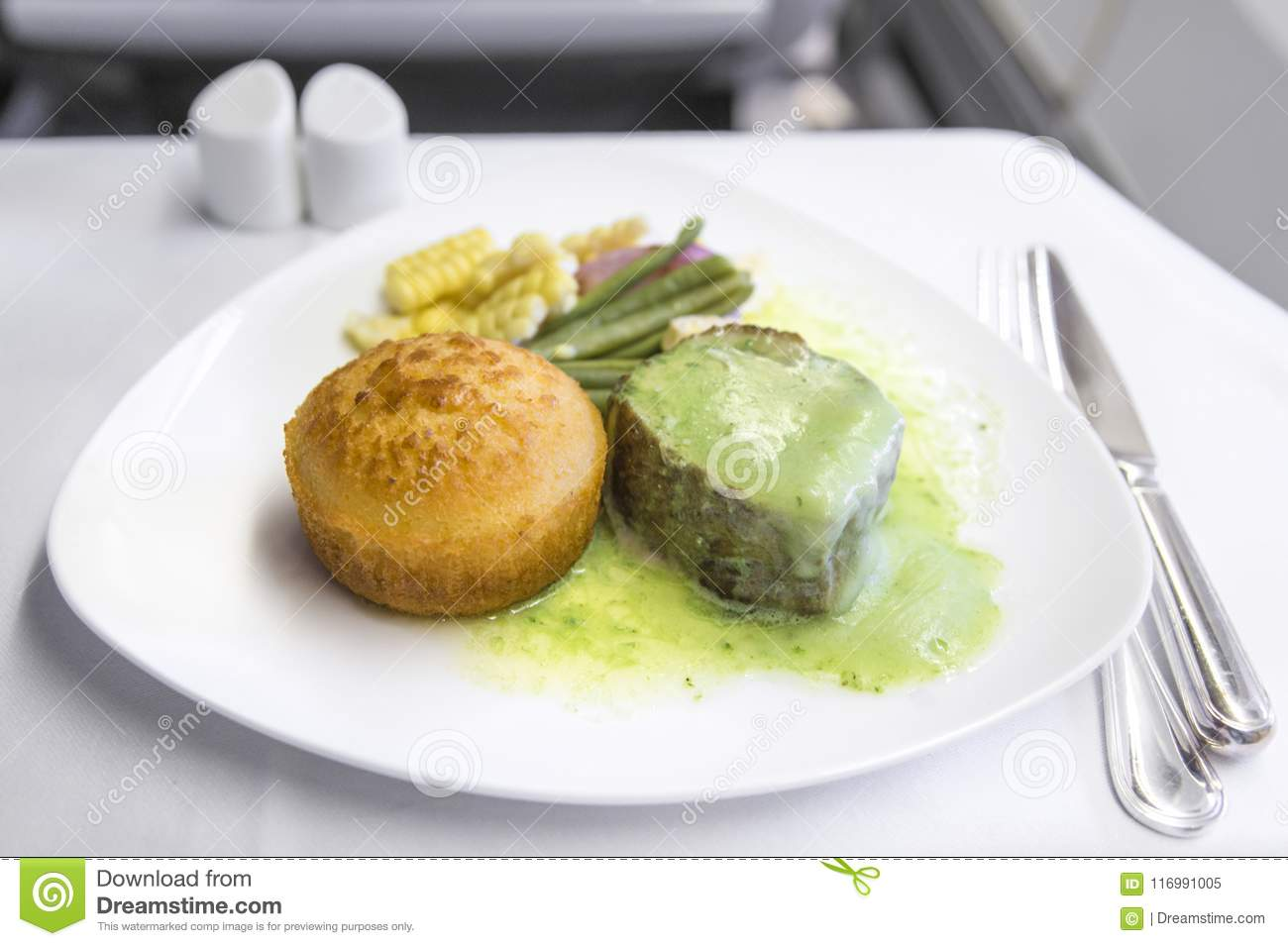 Set inflight meal steak on a tray, on a white table