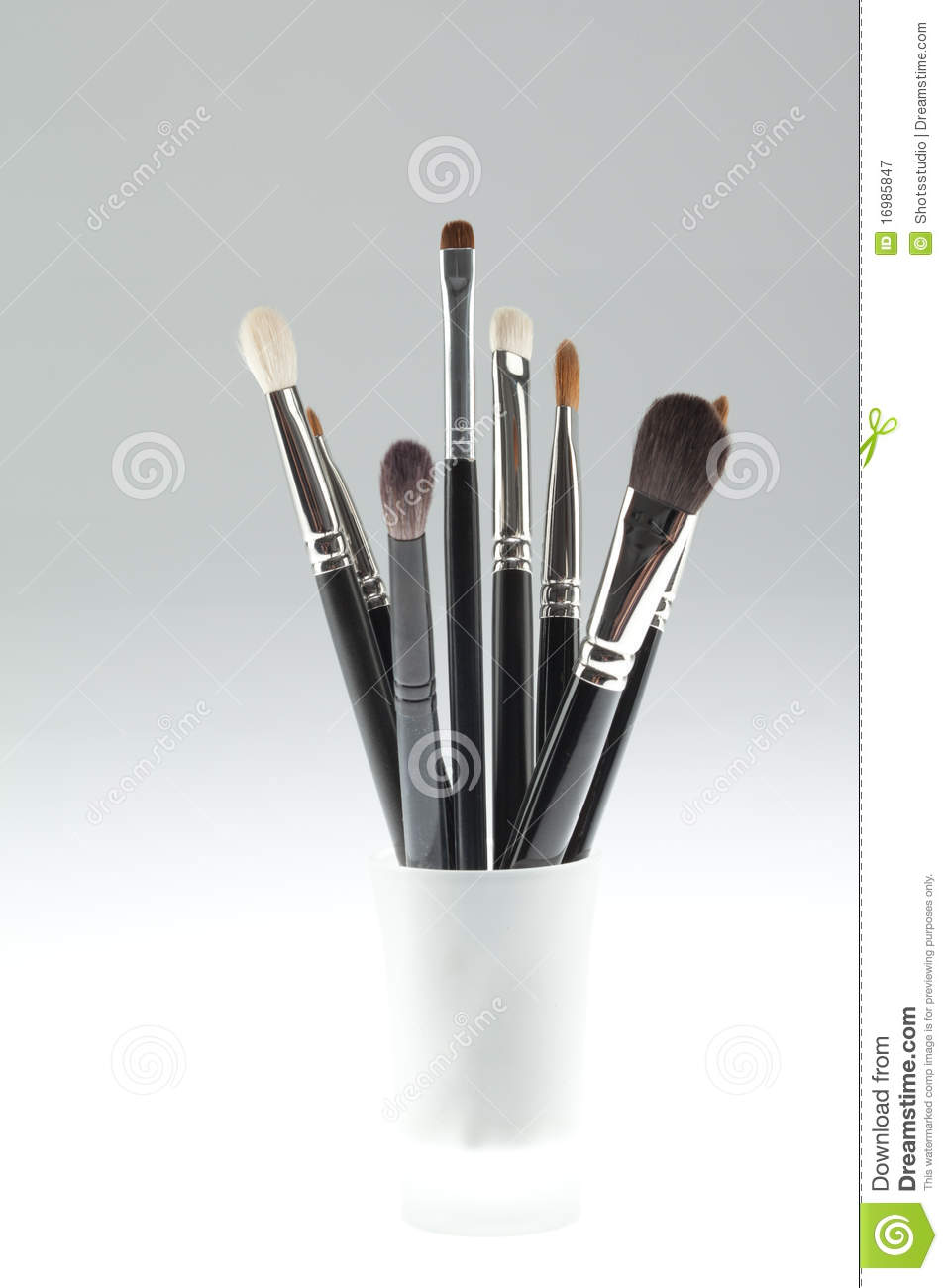 A set of make-up brushes set in a small glass