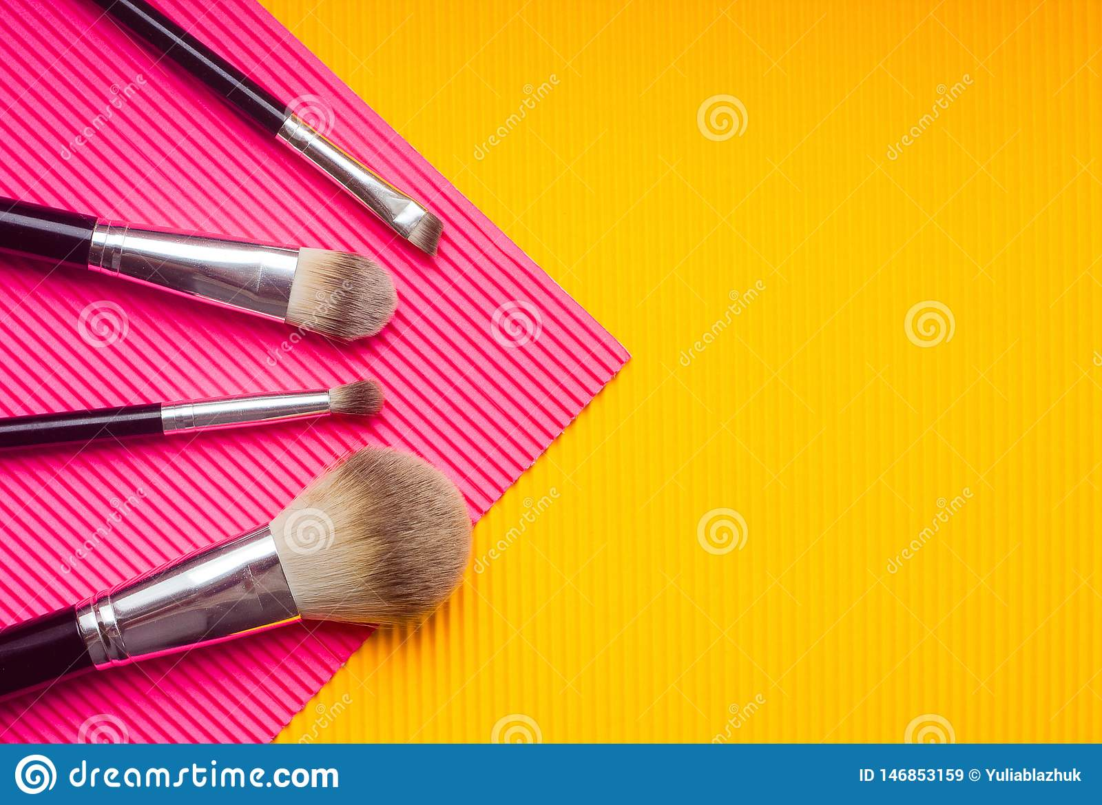 Set of makeup brushes against multicolor background. Top view point, flat lay