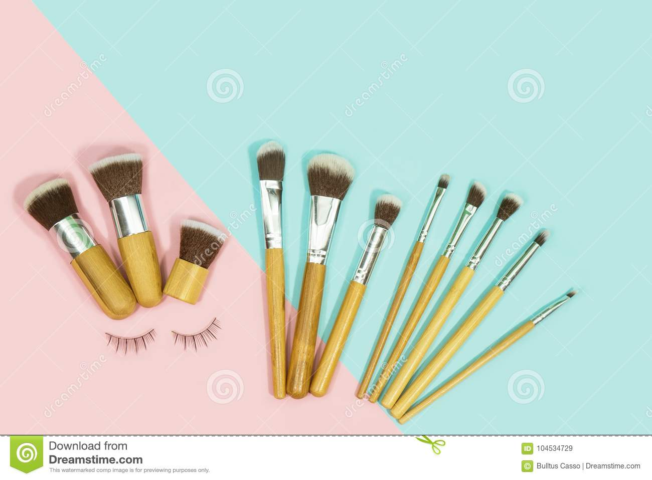 Set of makeup brushes on pink and aqua colored composed stock