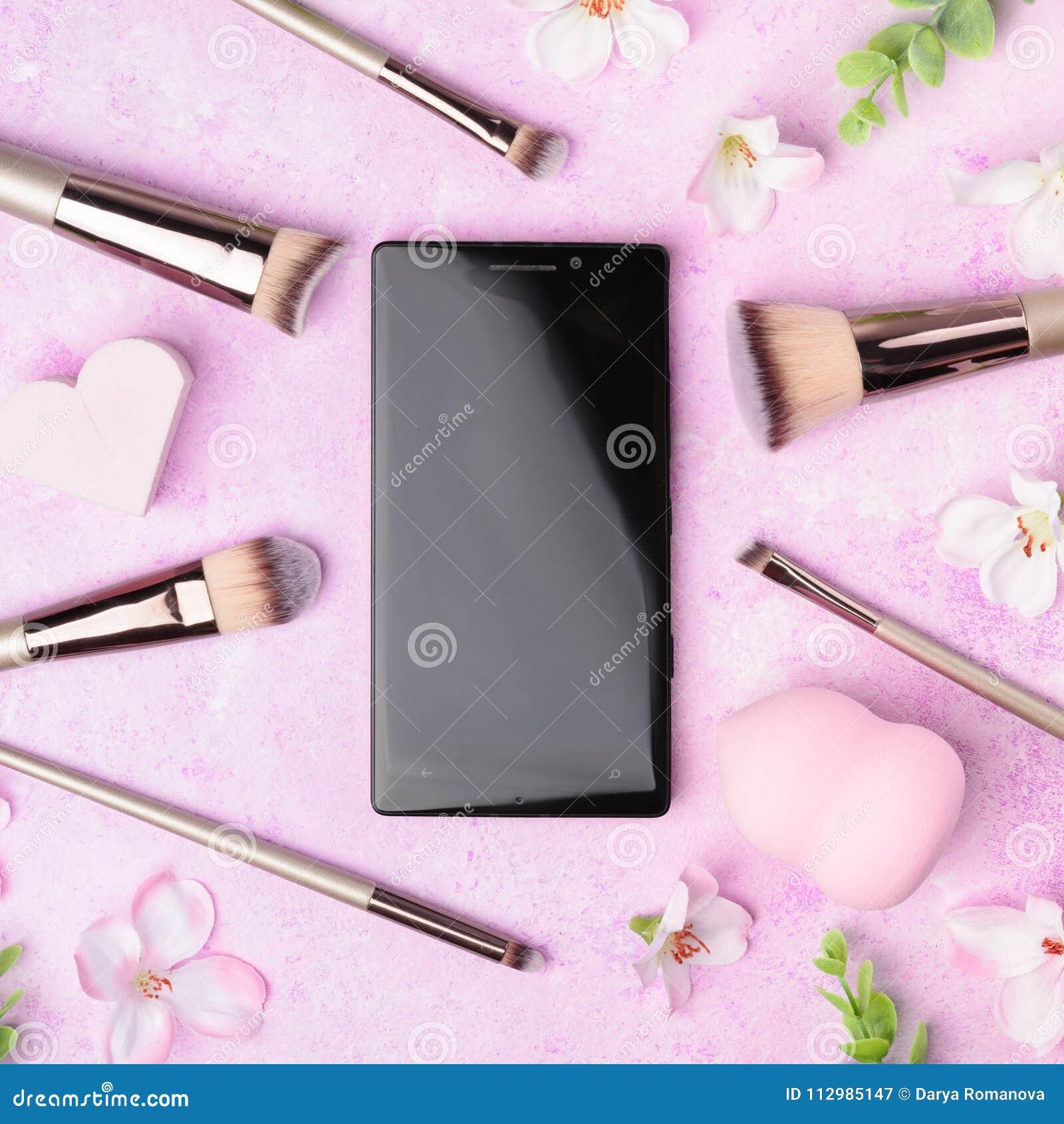 Set of makeup brushes on pink background.