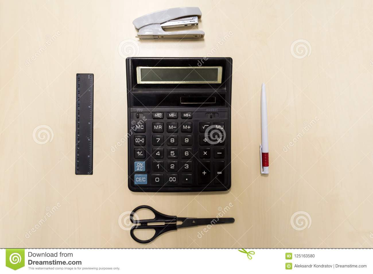 A set of office tools consisting of a calculator, pen, stapler,
