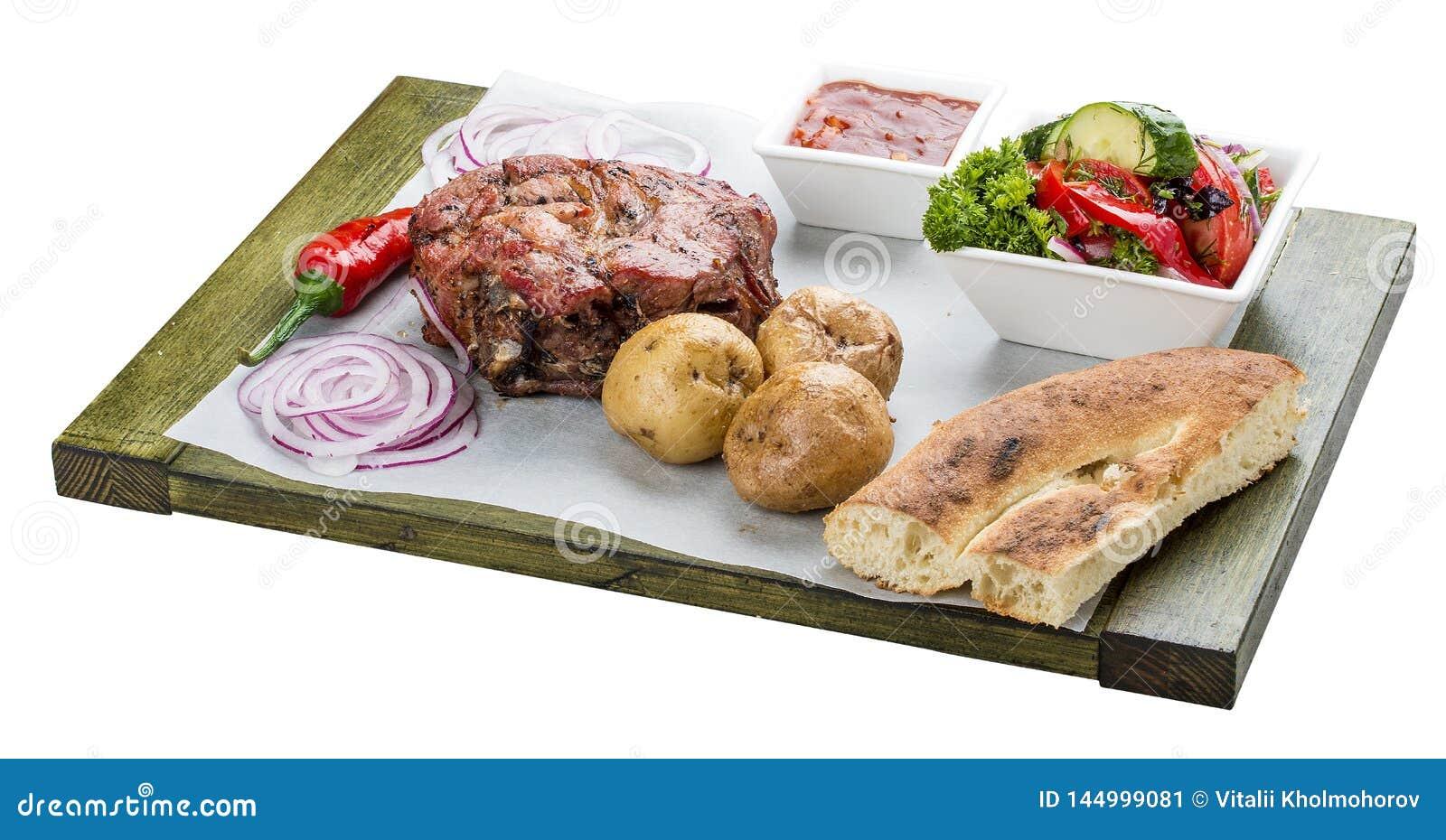Set of pork steak, vegetable salad, potatoes and sauce. Chalagach