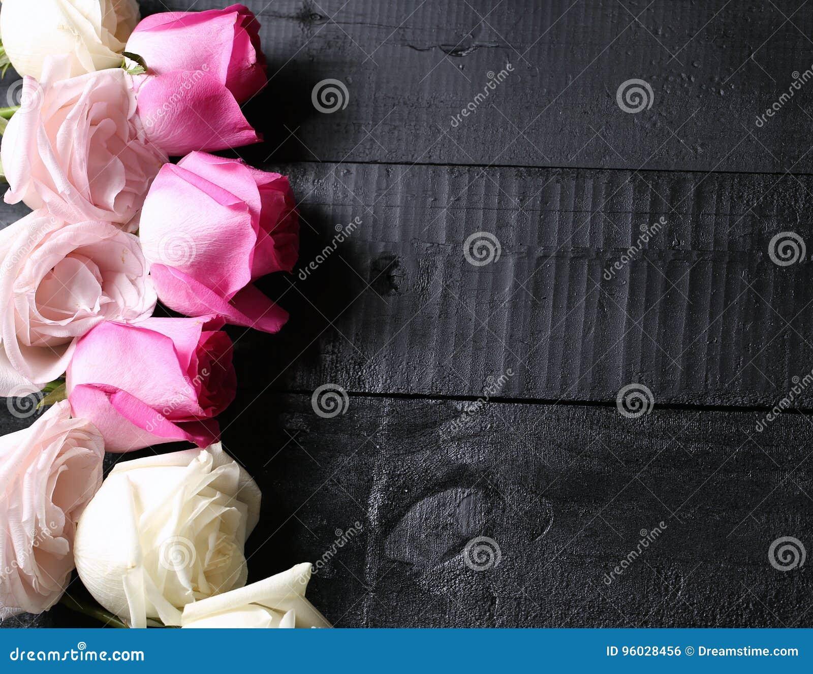 Set purpur, białych i żółtych róże na czarnym drewnianym tle,