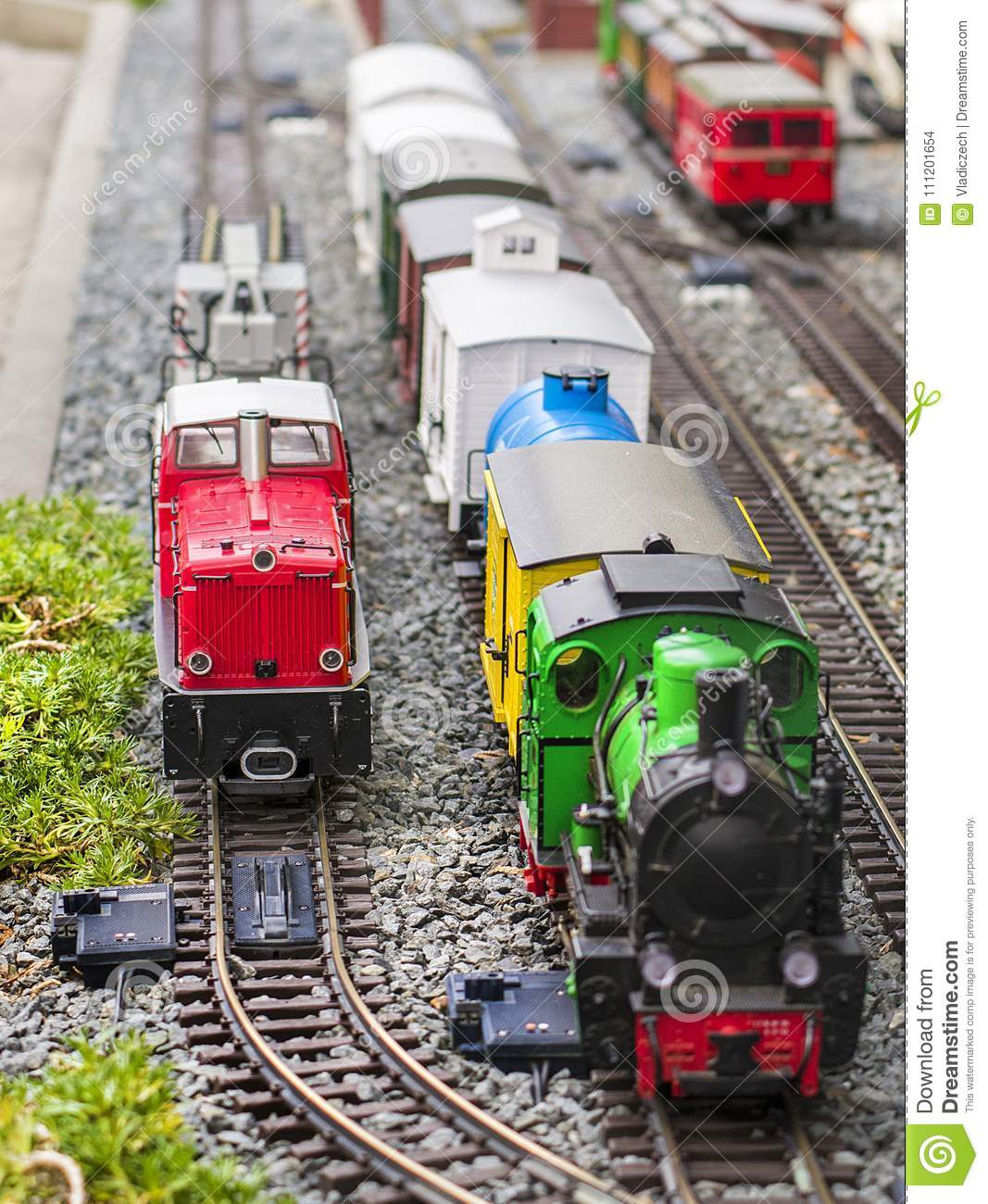 Set of red electric model railway locomotive and layout with a station and whole scene with features.