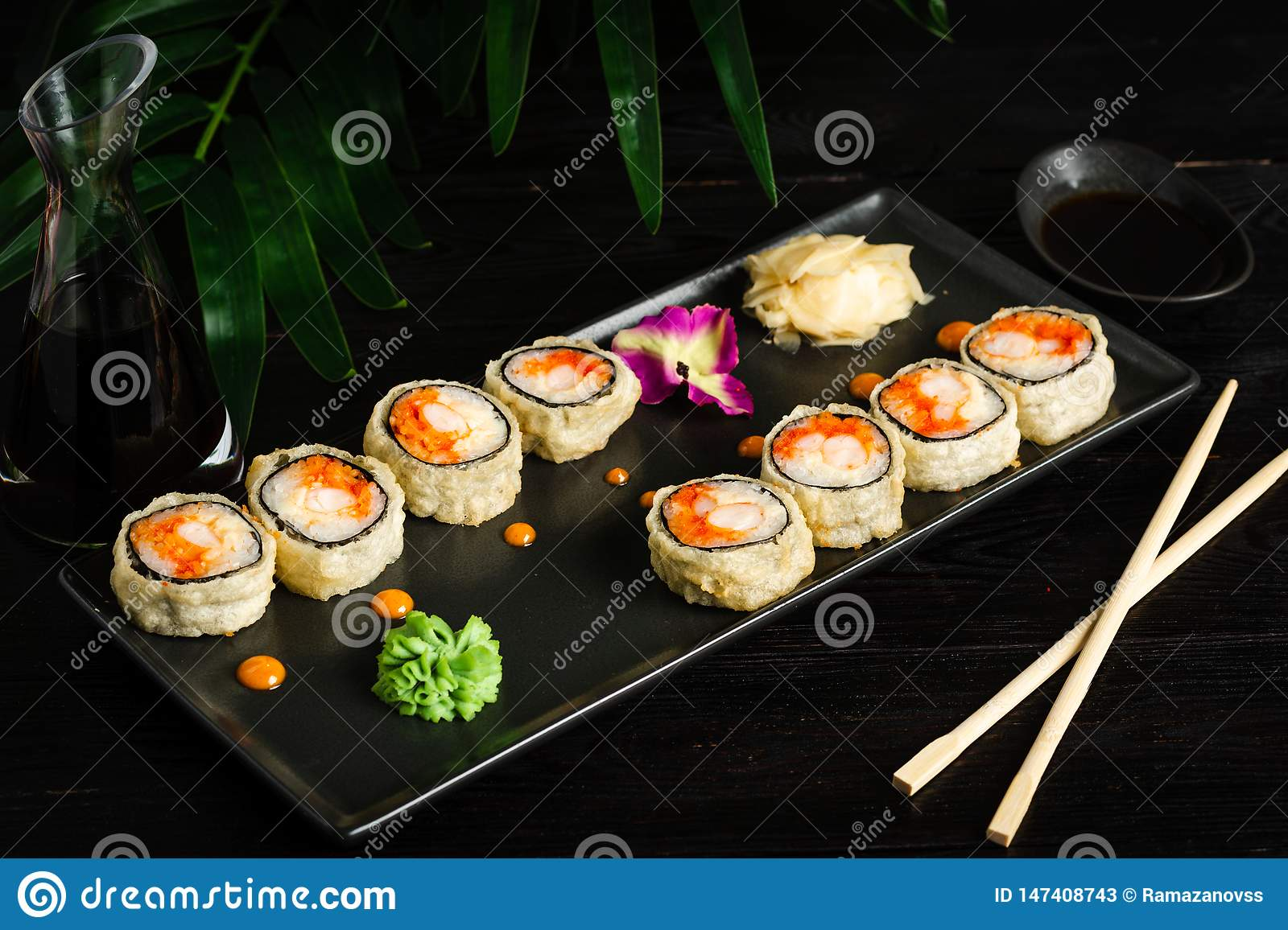 set of sushi rolls on a black plate on a black wooden background with green leaves of a houseplant