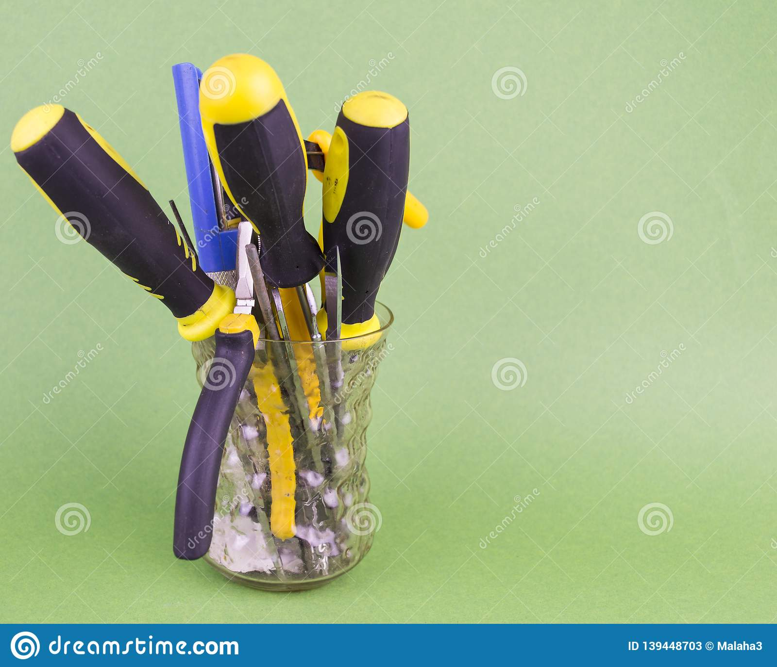 A set of tools in the glass - screwdrivers, pliers, nibs, yellow-black natfelas on a green background, there is an empty space to