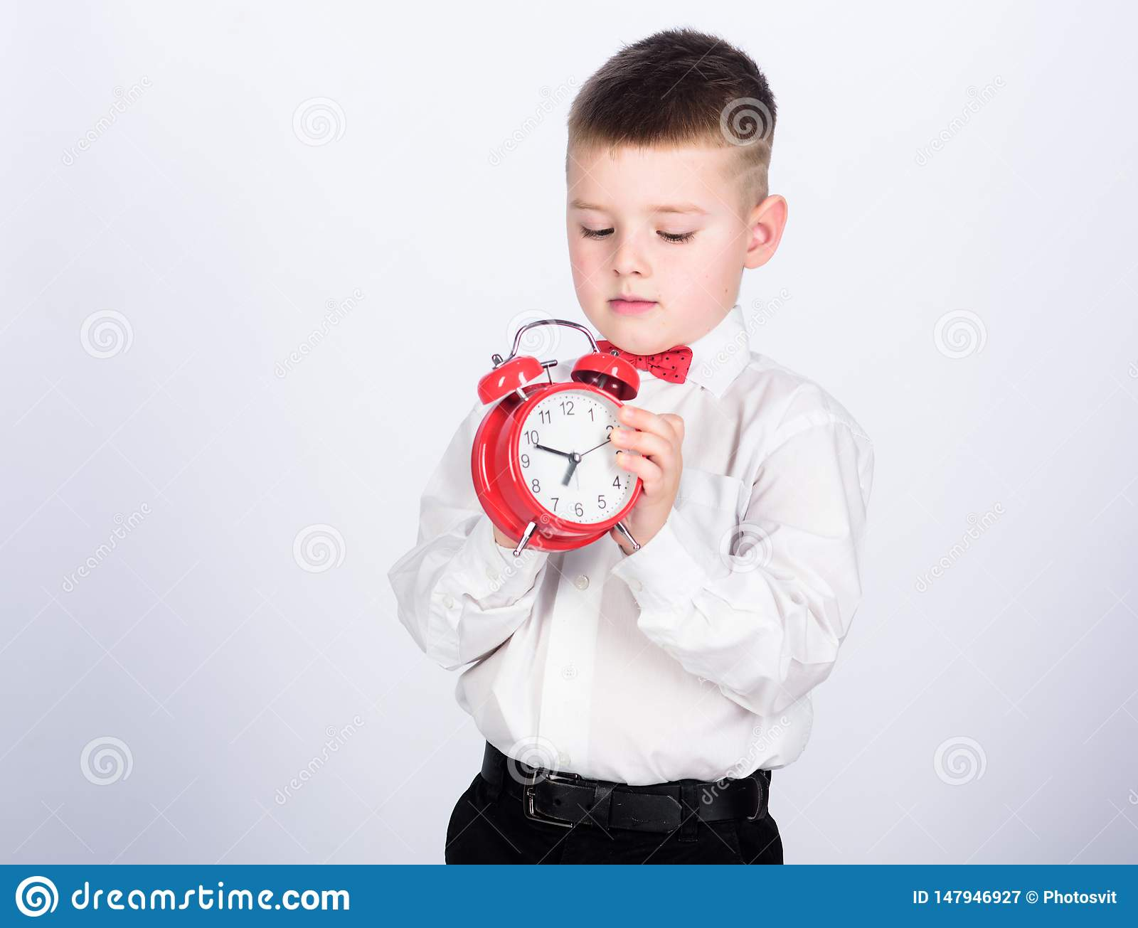 Set up alarm clock. Child little boy hold red clock. It is time. Schedule and timing. Morning routine. Schoolboy with