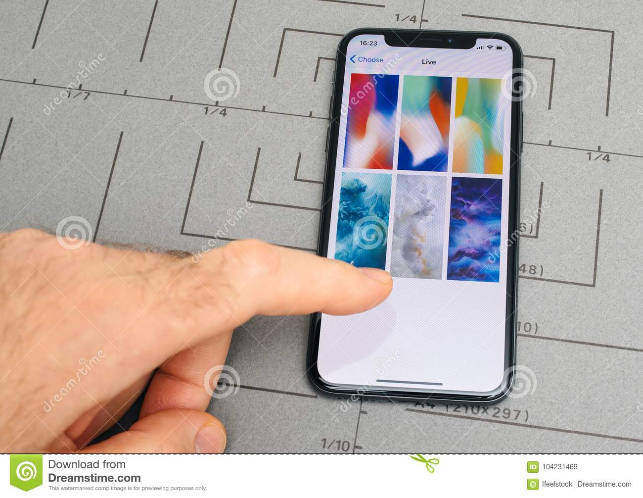 Paris, France - Nov 9, 2017: male hand touch selecting New Apple iPhone X 10 smartphone screen after unboxing and selecting live wallpaper