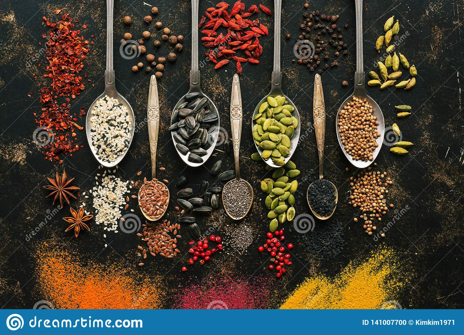 A set of varied seeds and spices in spoons on a dark background. Top view, flat lay. Multicolored spices