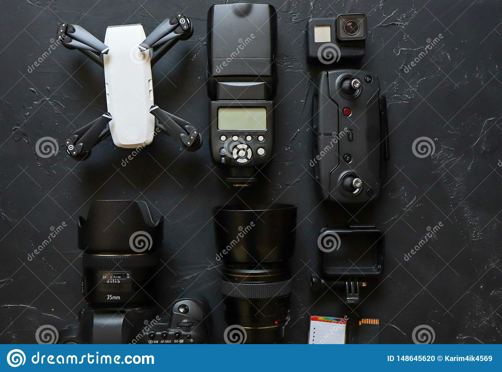 Set of videographer on a black background. Digital camera, memory card, action camera, drone, remote control and camera. Top view