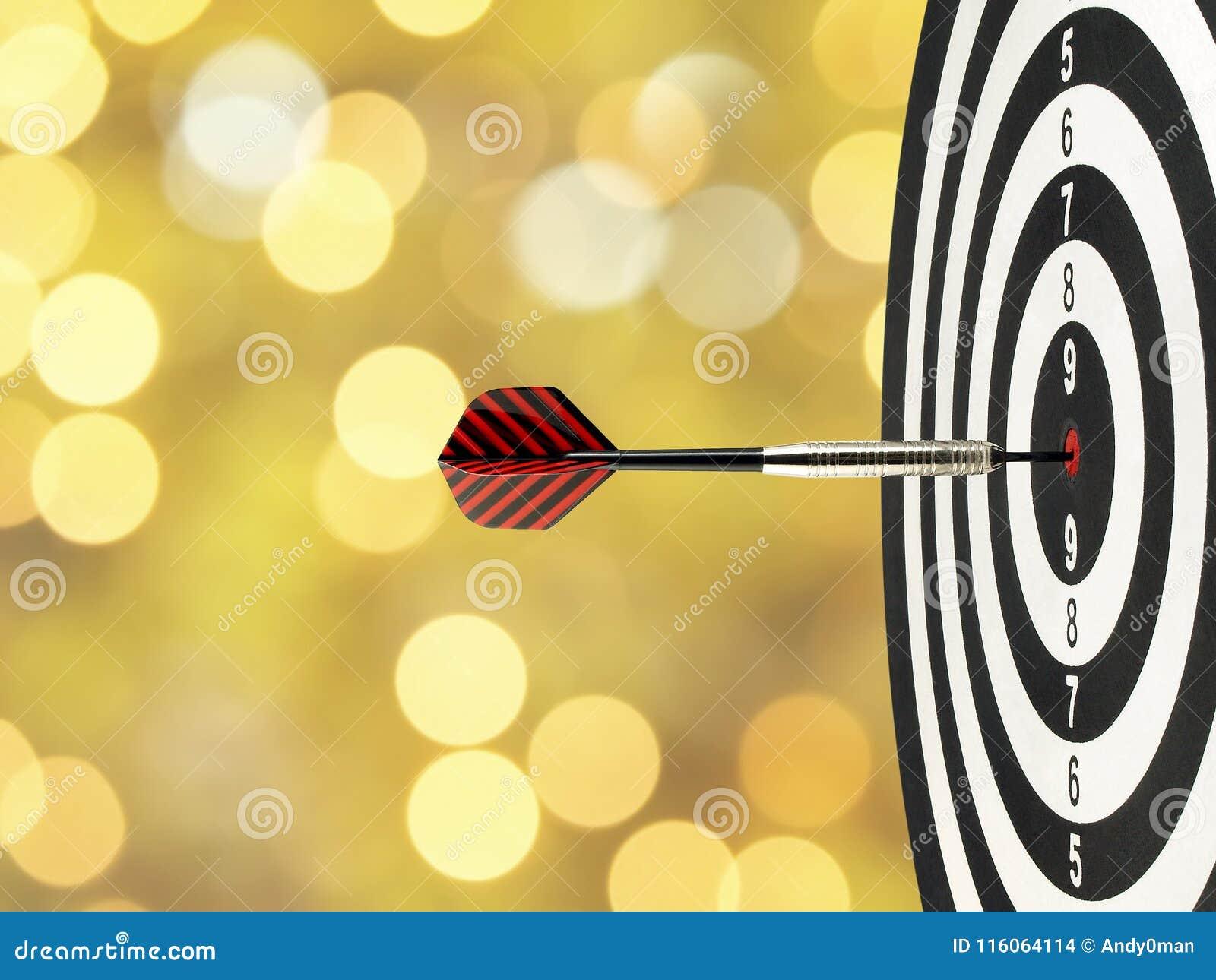 A seta do dardo do close-up que bate no centro do alvo no bullseye no alvo de madeira com ouro amarelo borrado ilumina o fundo do