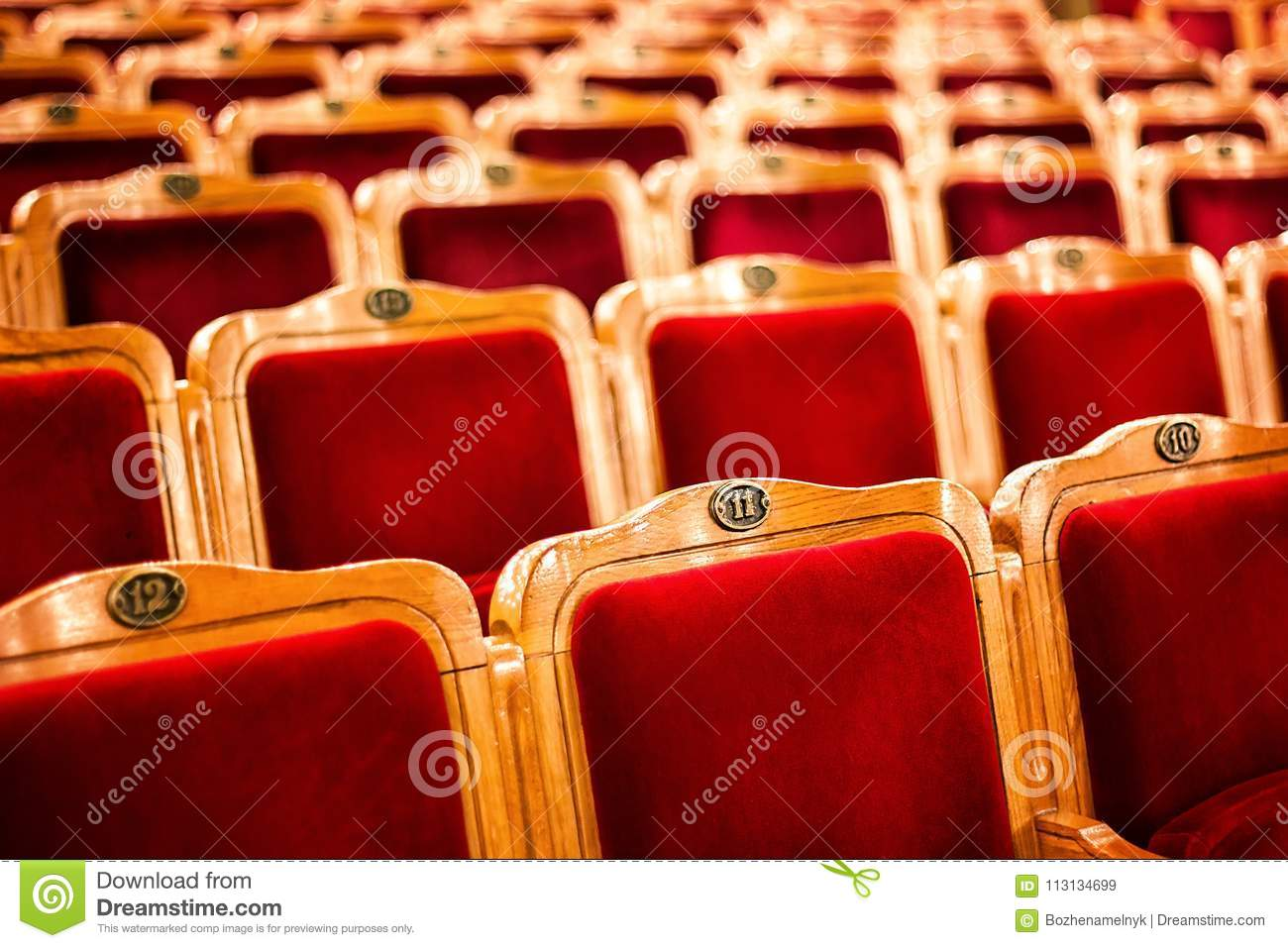 Sets on an empty theatre, taken with selective focus and shallow depth of field. Empty vintage red seats with numbers, teather cha
