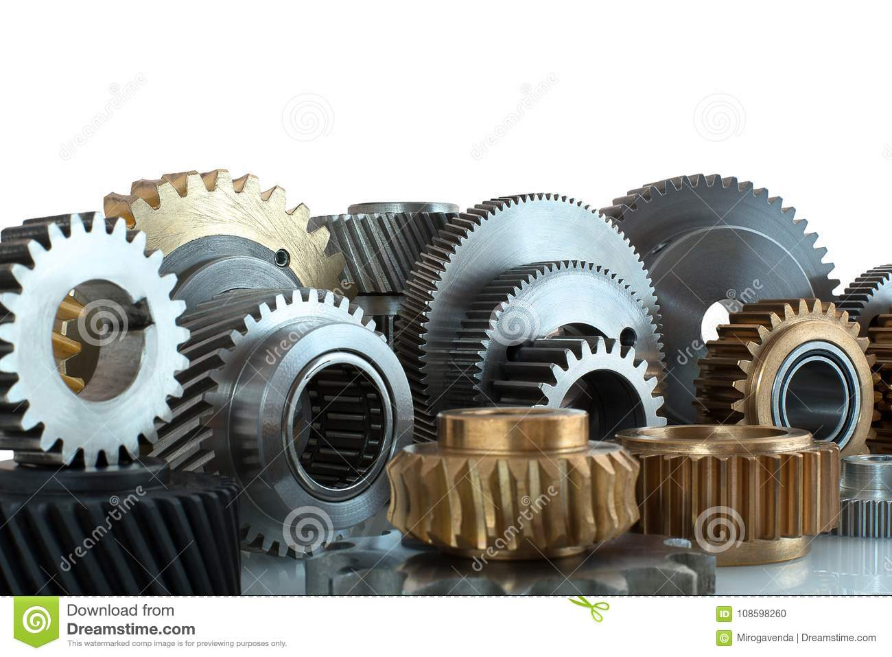Sets of gears, cogwheels made of steel and brass isolated on white background with shadow reflection. Helical and spur gears,some