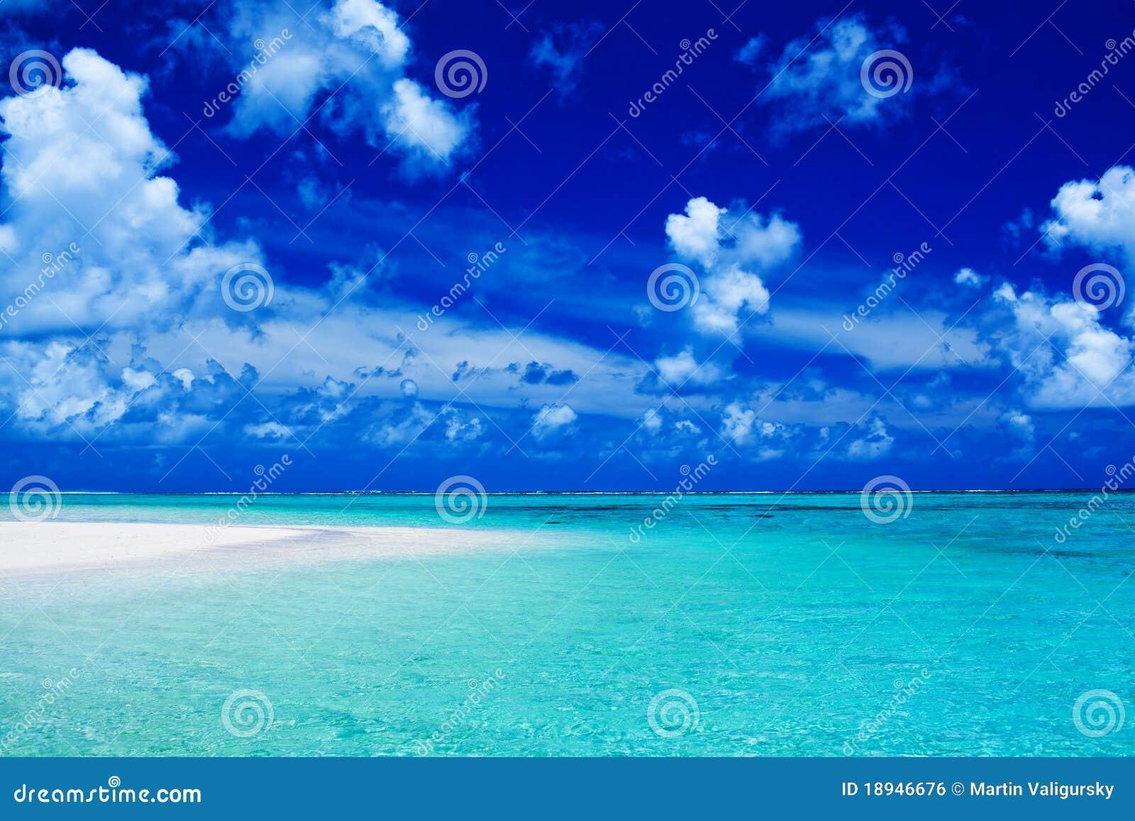 Setzen Sie mit blauem Himmel und vibrierenden Ozeanfarben auf den Strand