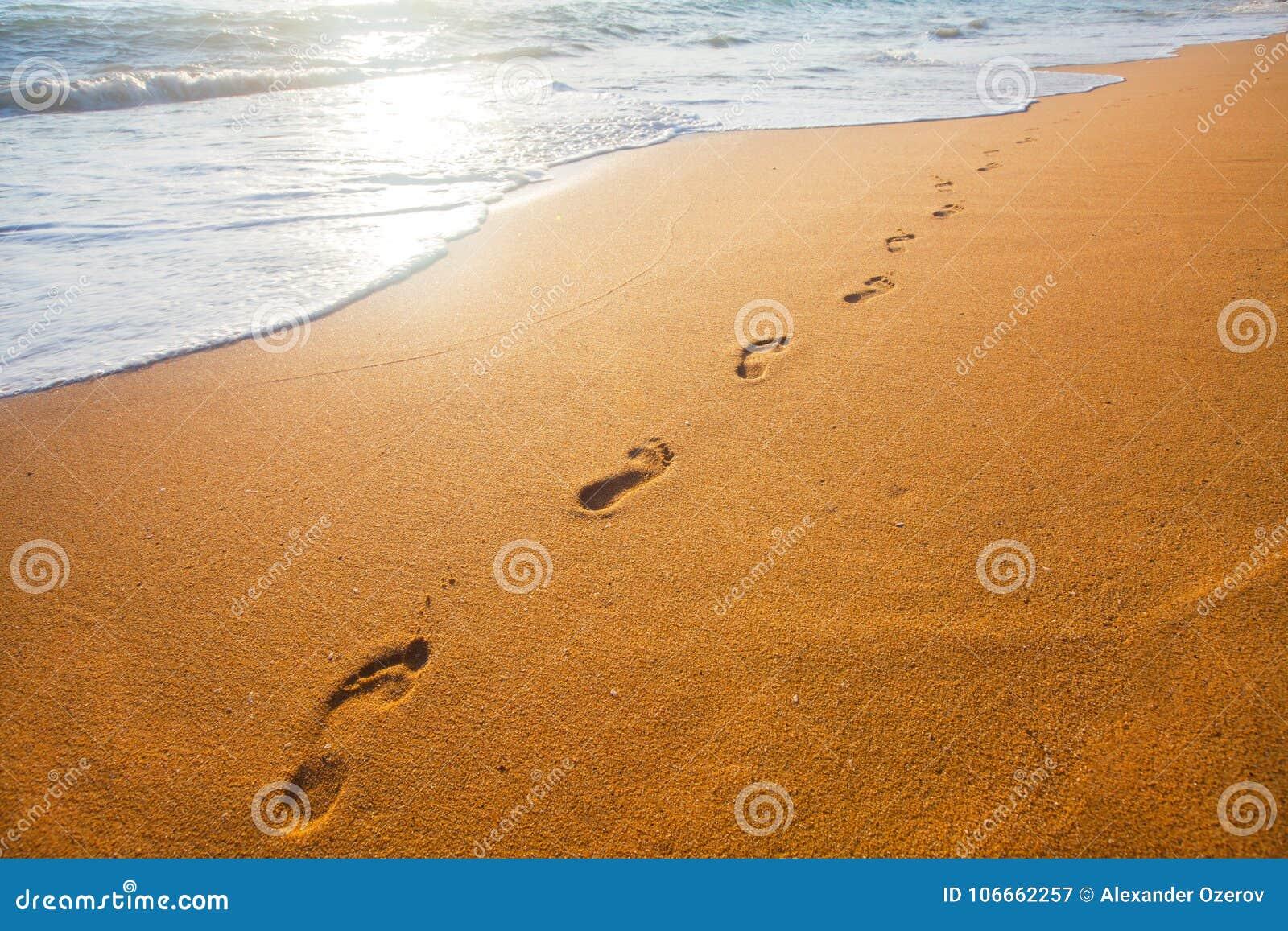 Setzen Sie, Welle und Abdrücke zur Sonnenuntergangzeit auf den Strand
