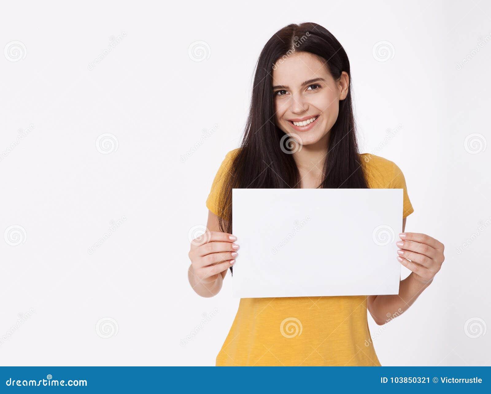 Seu texto aqui Jovem mulher bonita que guarda a placa vazia vazia Retrato do estúdio no fundo branco Modelo para o projeto