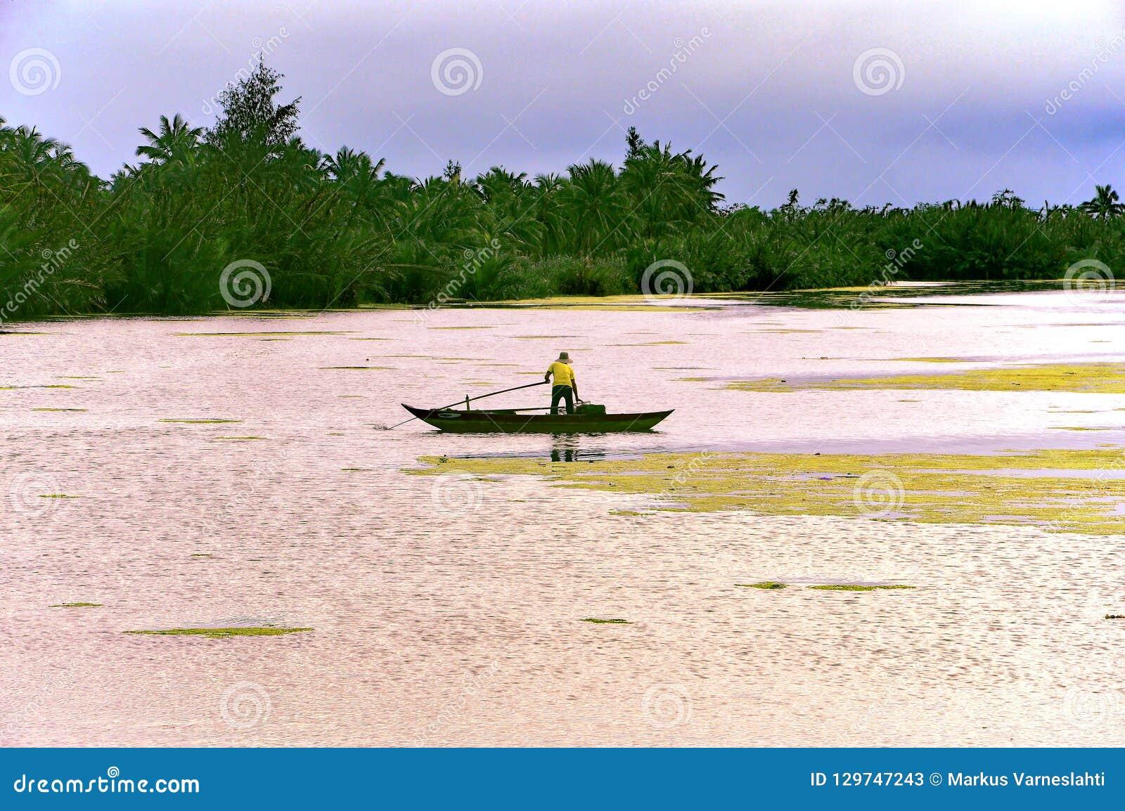 Seul pêcheur dans son bateau à la rivière