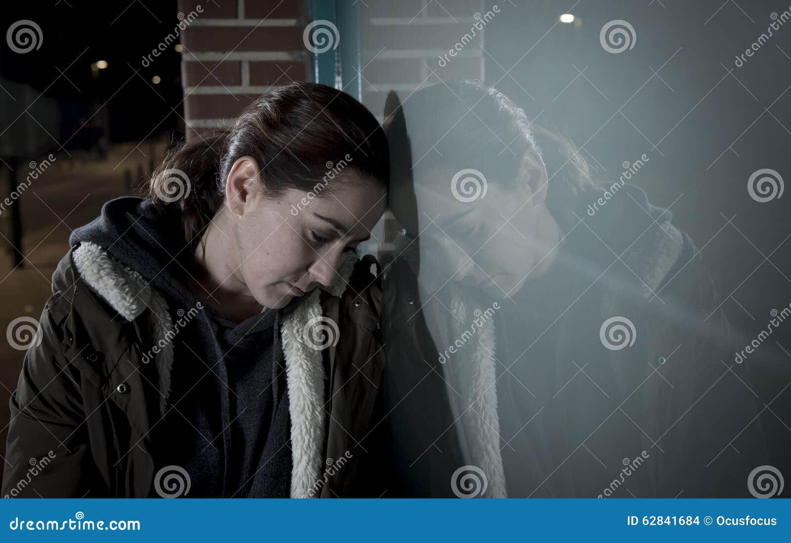 Seul penchement de femme triste sur la fenêtre de rue à la dépression de souffrance de nuit pleurant en douleur
