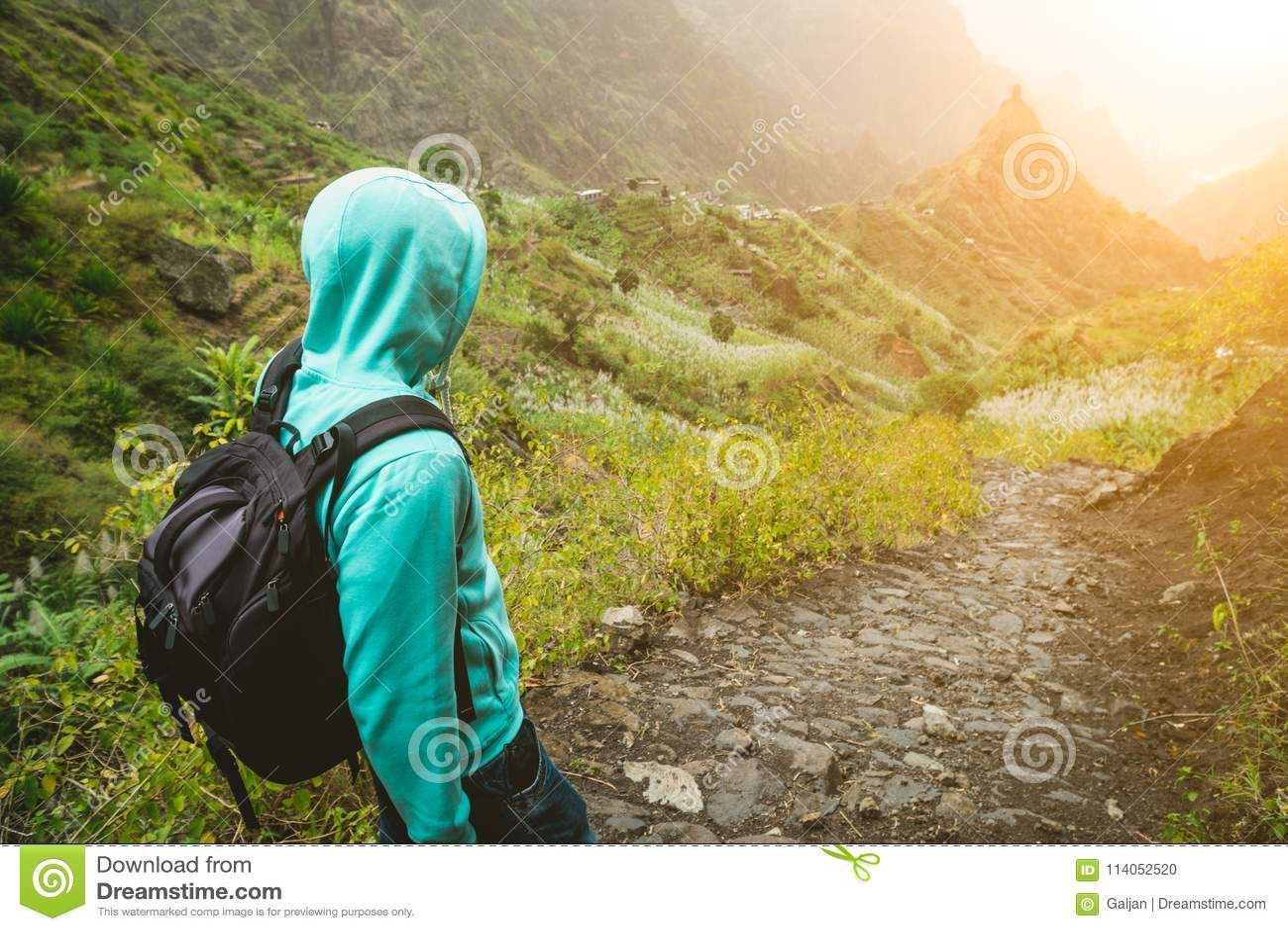 Seul voyageur avec le sac à dos descendant la traînée pavée en cailloutis de trekking vers la vallée verte Sun évase sur le hozir