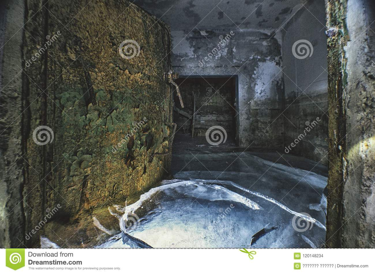 Rusty protective airtight door, in an abandoned flooded shelter, in ice