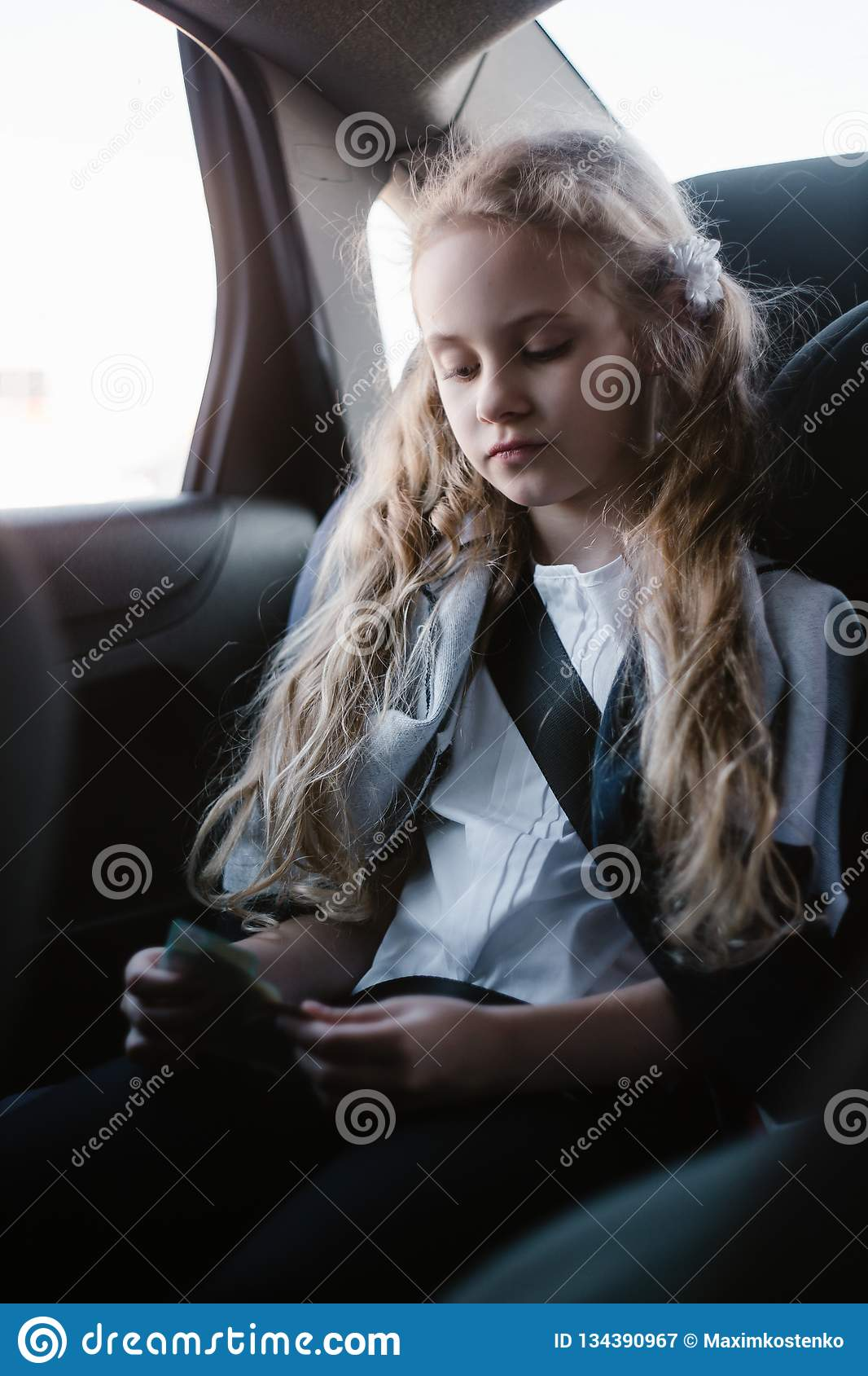 Seven-year charming girl sitting in a children`s car seat