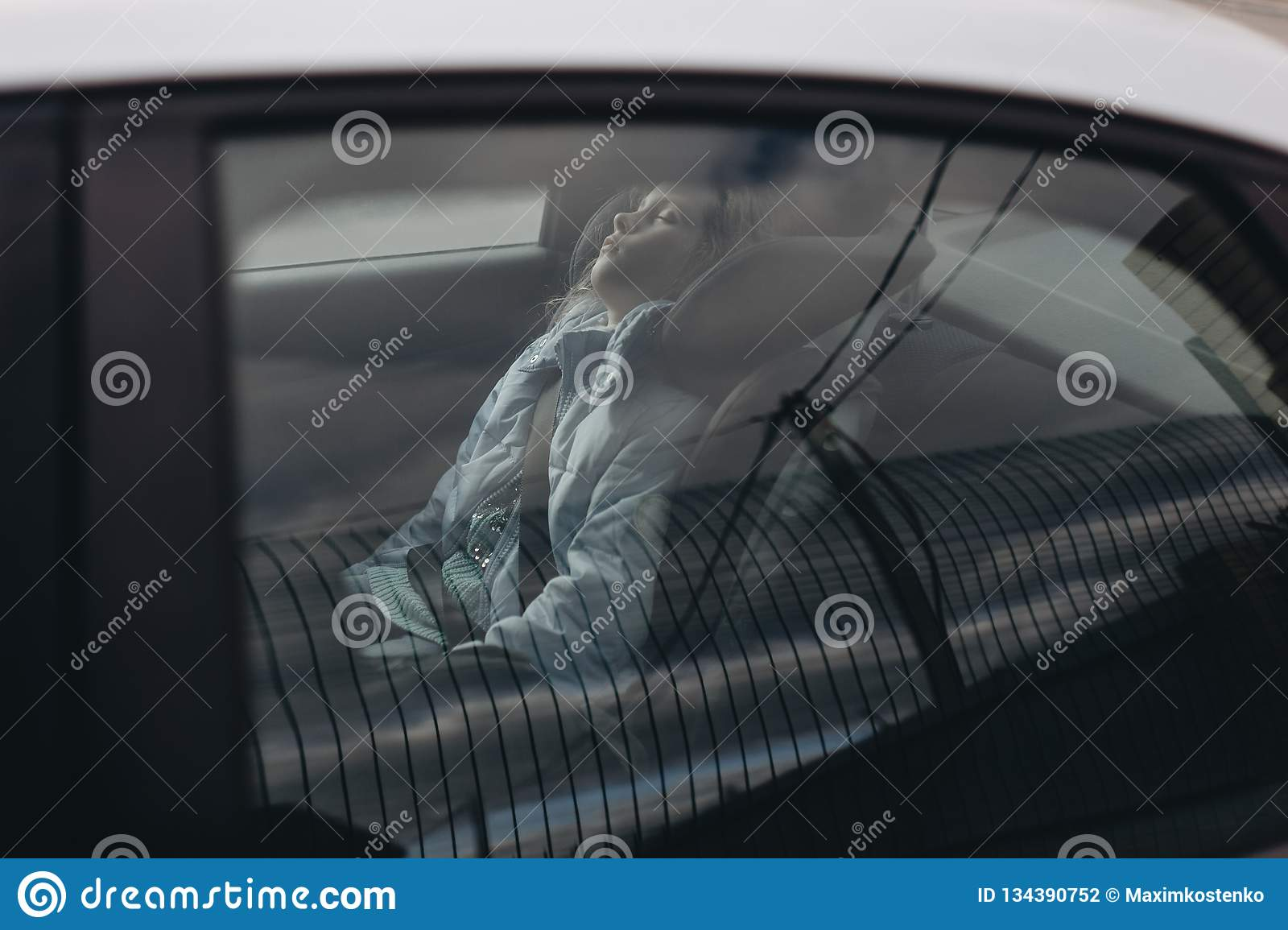 Seven-year charming girl sleeping in a children`s car seat