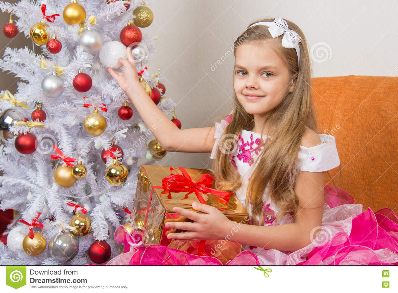 Seven-year girl in beautiful dress sits with a gift and holding a Christmas ball in hands
