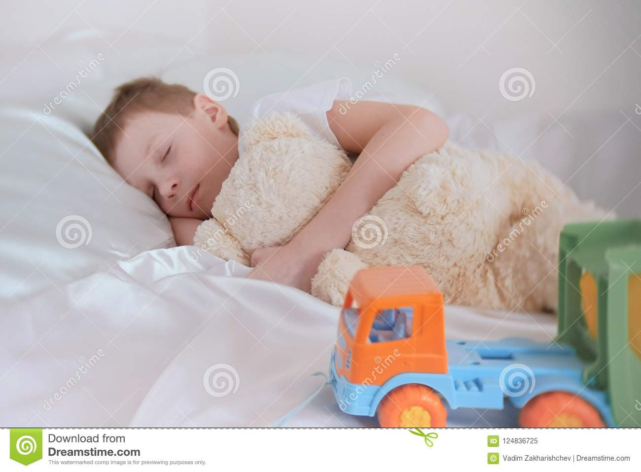 Seven-year-old boy sleeping with his toys bear and plastic car.