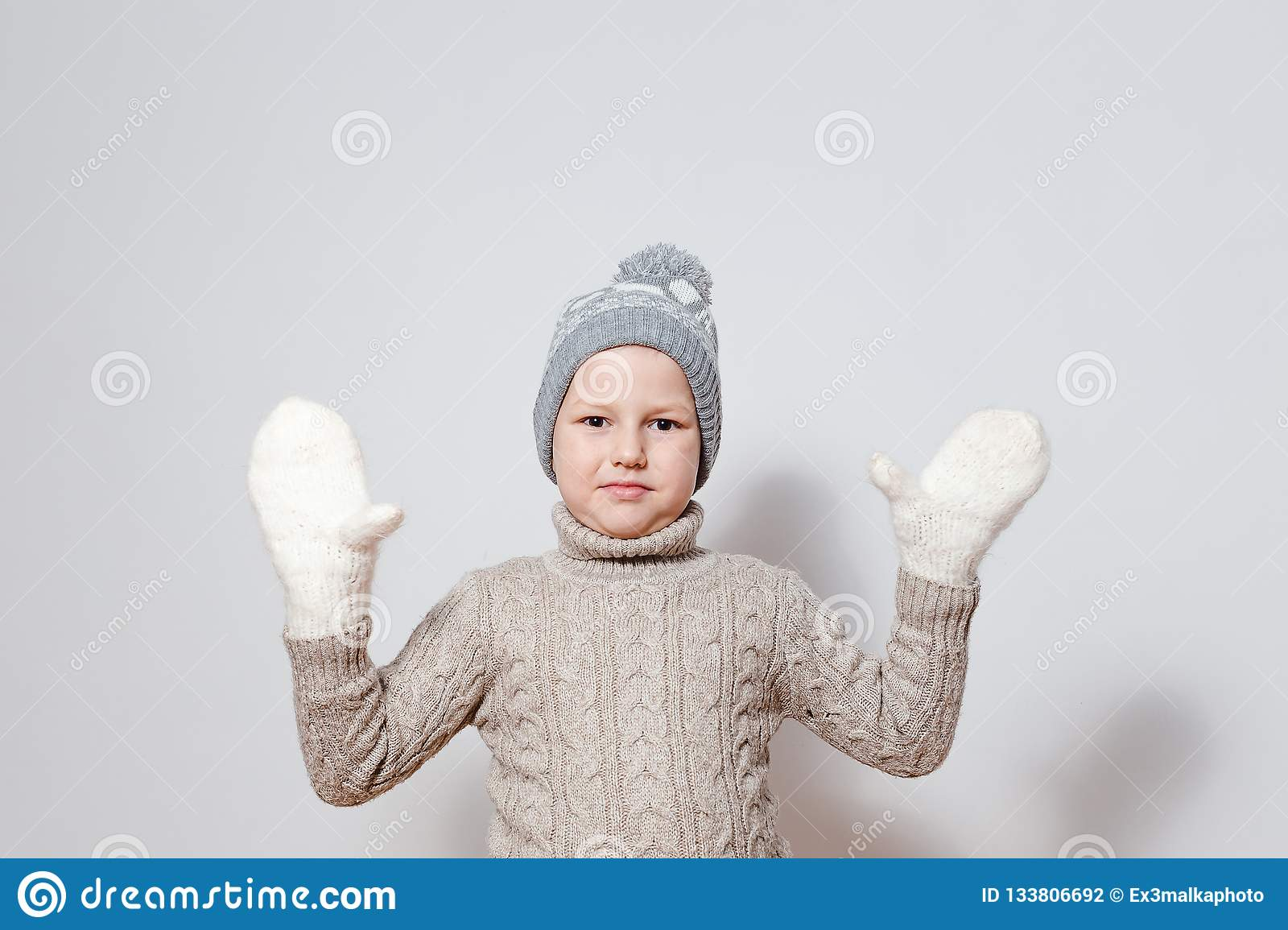 Seven-year-old boy in white knitted mittens and sweater spreads his hands to the sides